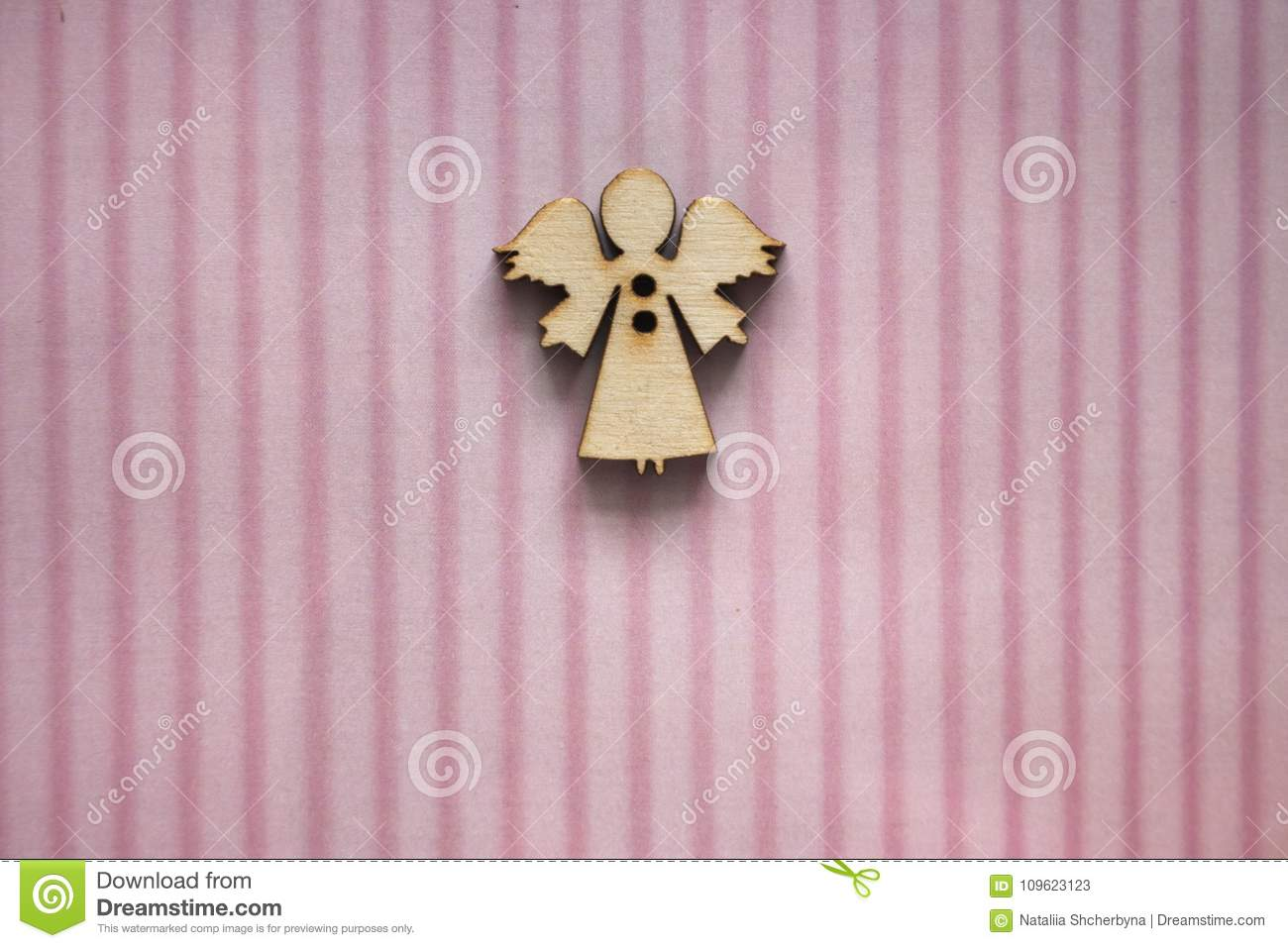 Small wooden angel figure on pink striped background. Greeting card design. Gift and present concept. Birthday background.