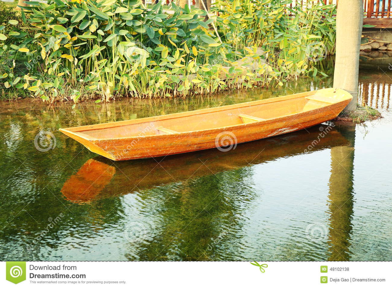 Small wooden boat on garden pond