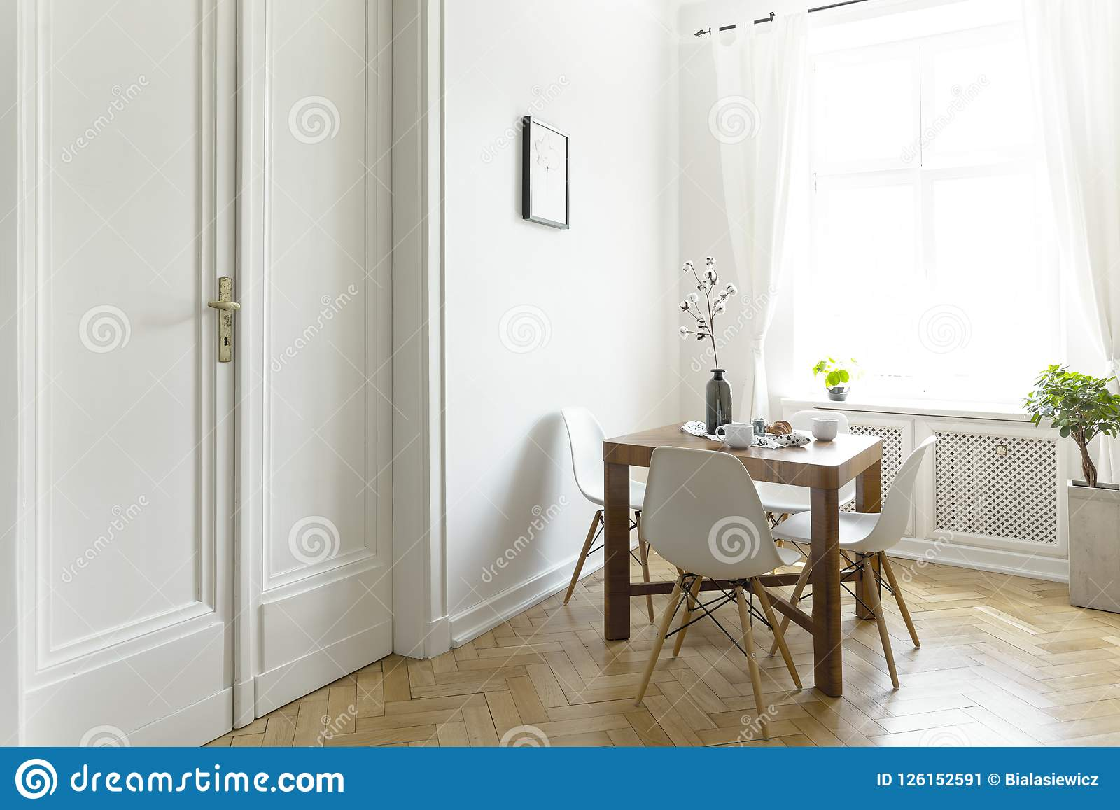 A Small Wooden Dining Table With Chairs In Sunny Room Interior White Walls