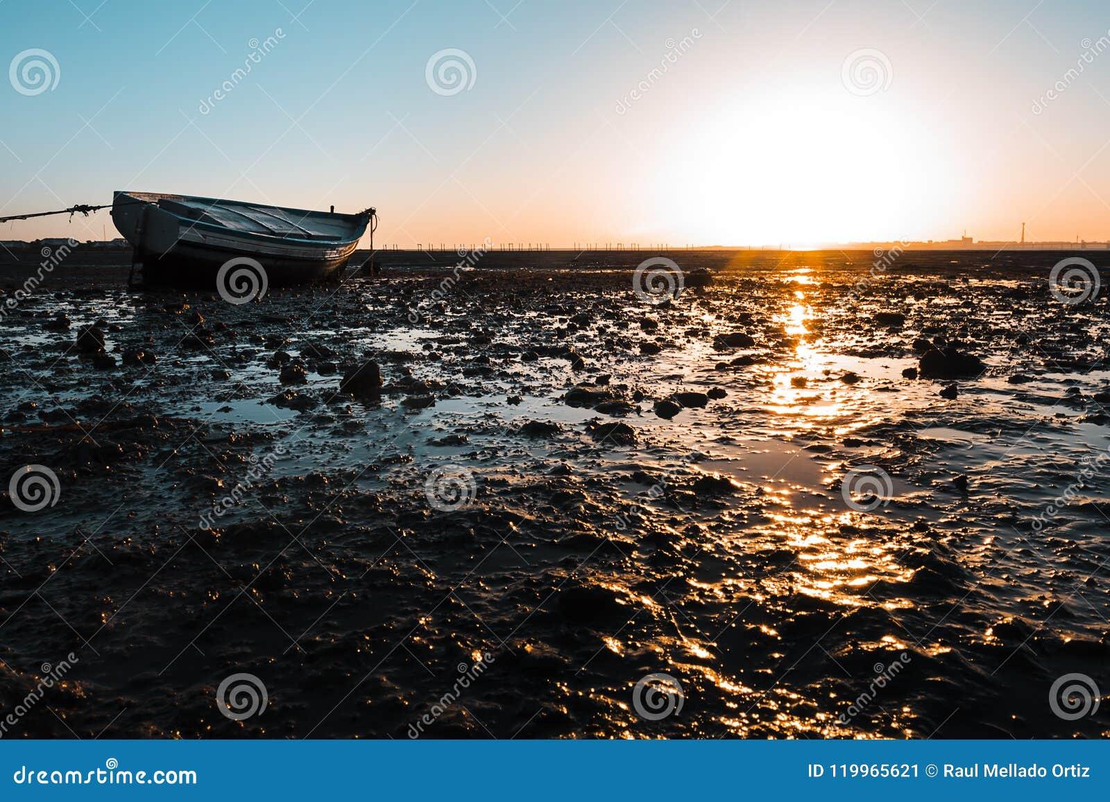 Sunset At Anchor Fishing Boat At Low Tide Stock Photo