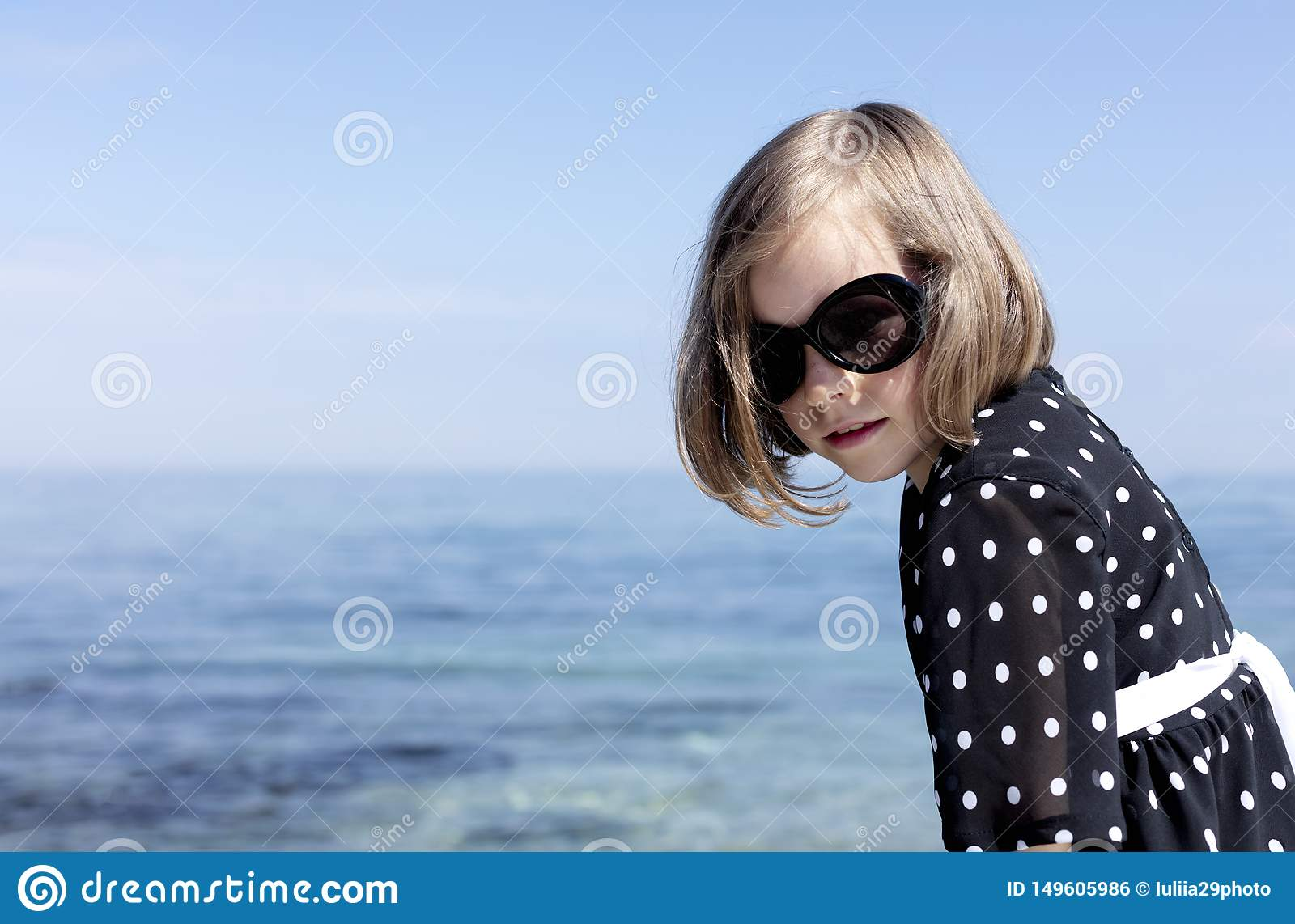 Small 7 years old pretty cheerful girl in a black  dress with white polka dots is standing on a wooden white pier