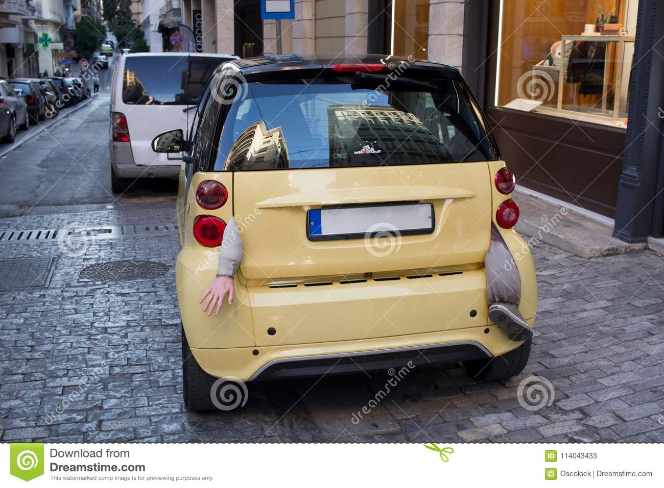 Small Yellow City Car With Body Parts Hanging From Boot Stock Image