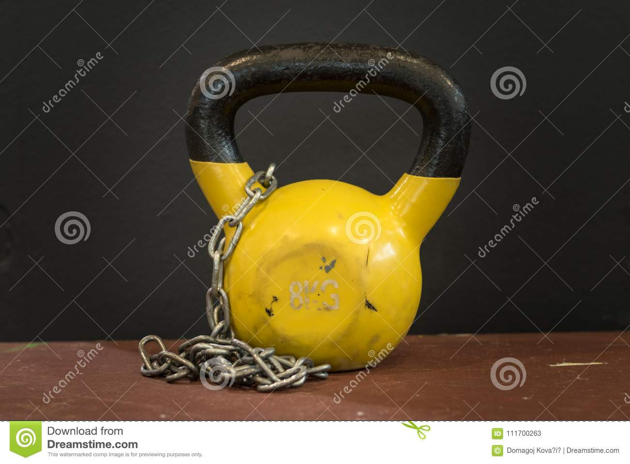 Small yellow eight kilograms heavy worn out kettlebell with silver chain against black background. Gym and fitness equipment