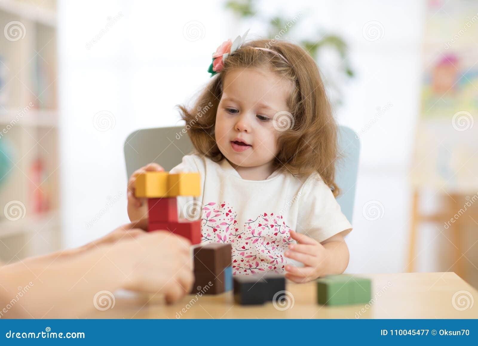Little child girl plays in kindergarten in Montessori preschool class.