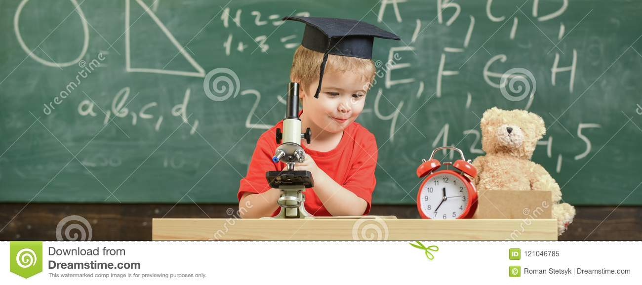 Smart kid concept. Child on happy face holds microscope. First former interested in studying, learning, education. Kid