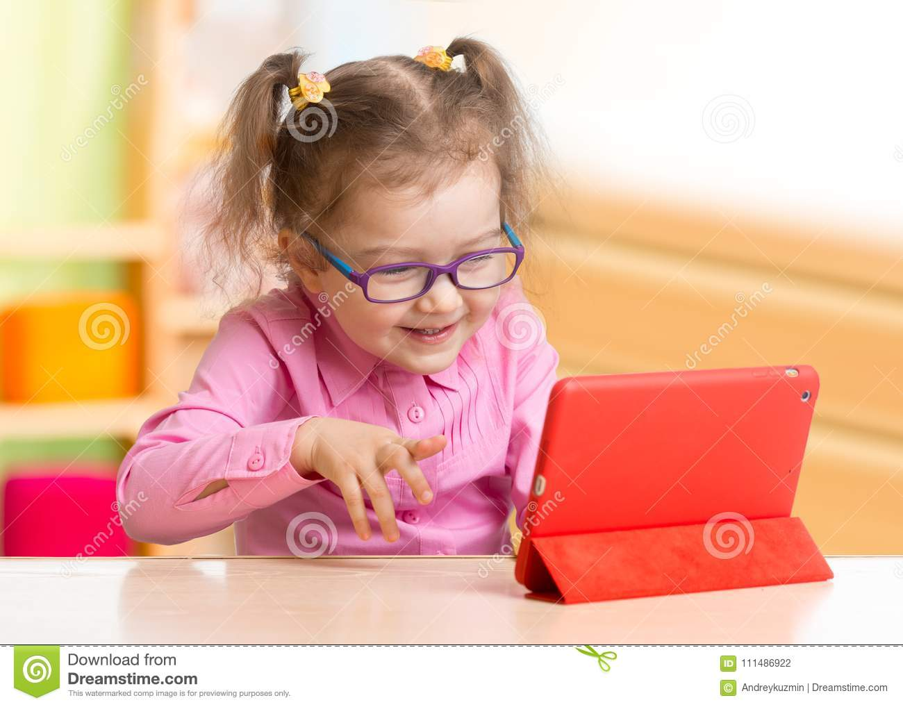 Smart kid in spectacles using tablet PC or e-book sitting at table in her room