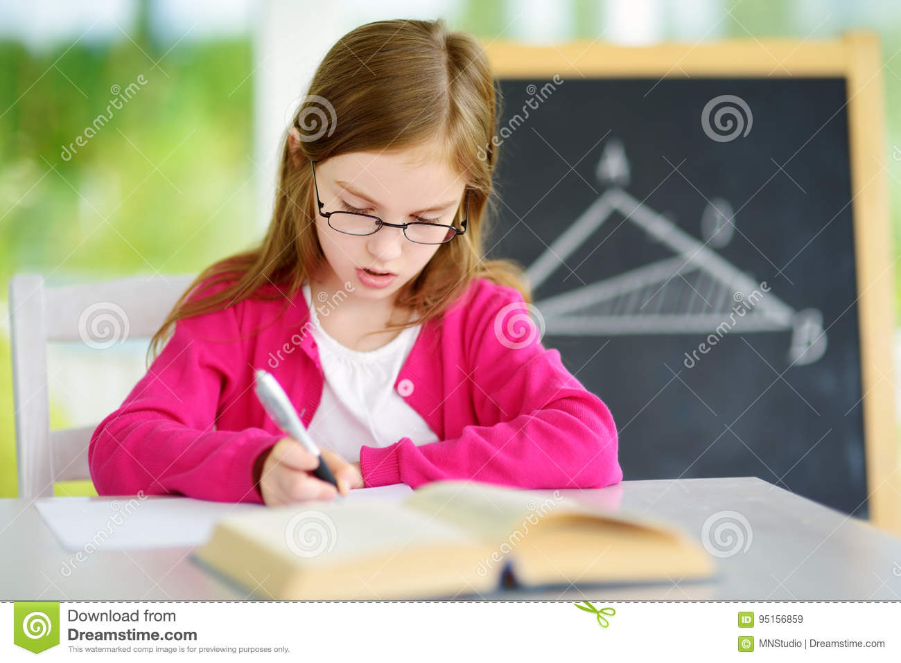 Smart Little Schoolgirl With Pen And Books Writing A Test In