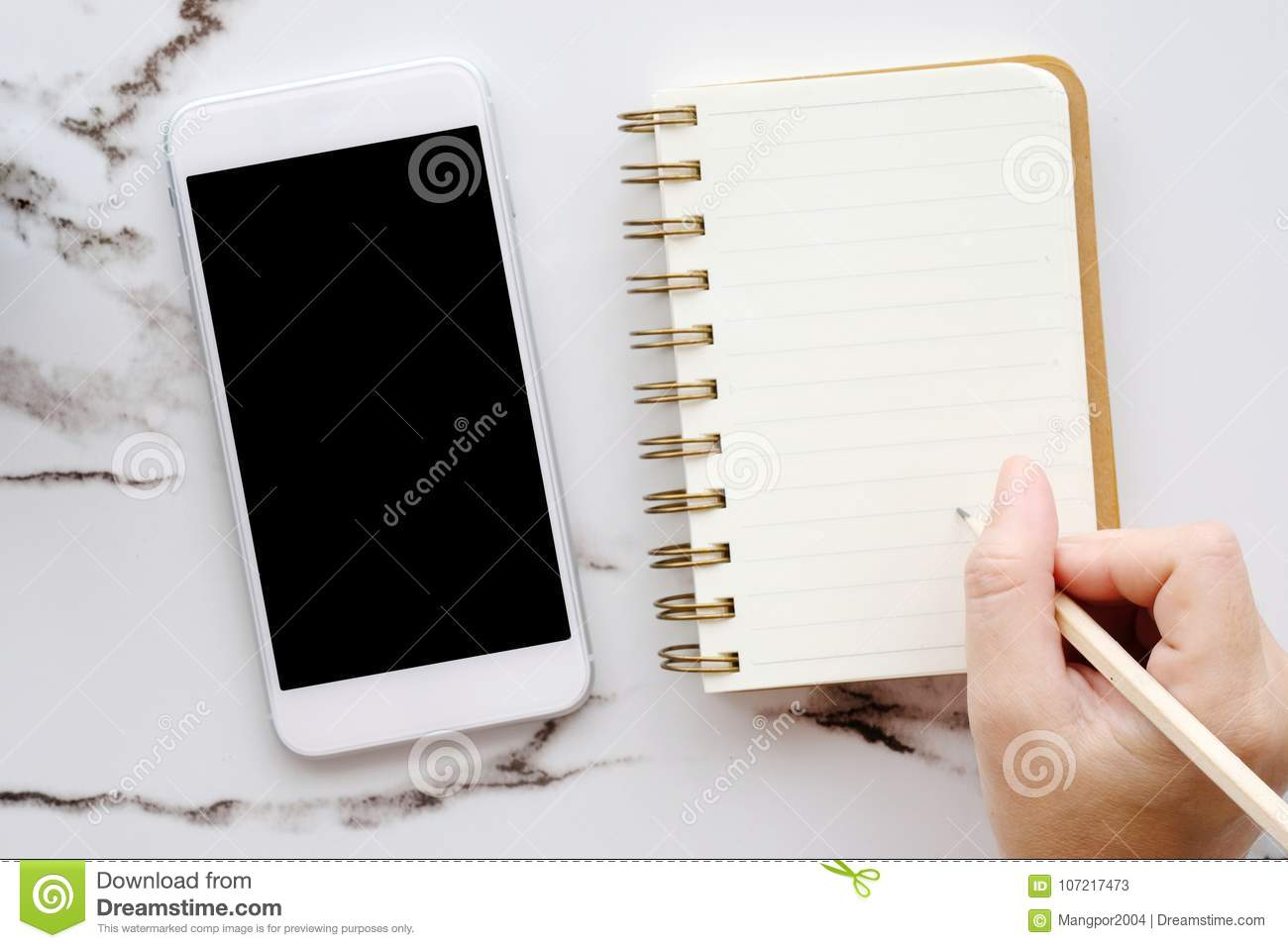 Smart phone with blank screen and hand holding pencil over blank