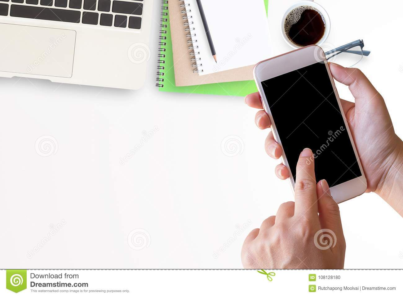 Smart phone in female hand with office desk with laptop
