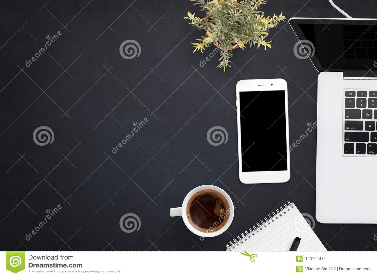 Smart phone and laptop on black office desk with copy space on left side