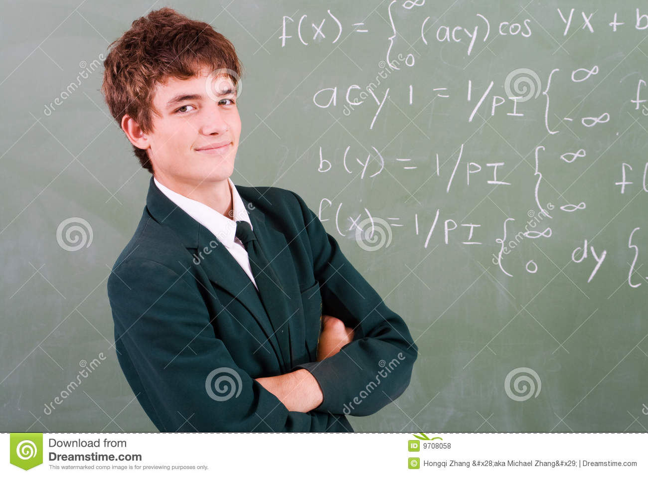 Young smart male high school student in front of blackboard with math ...