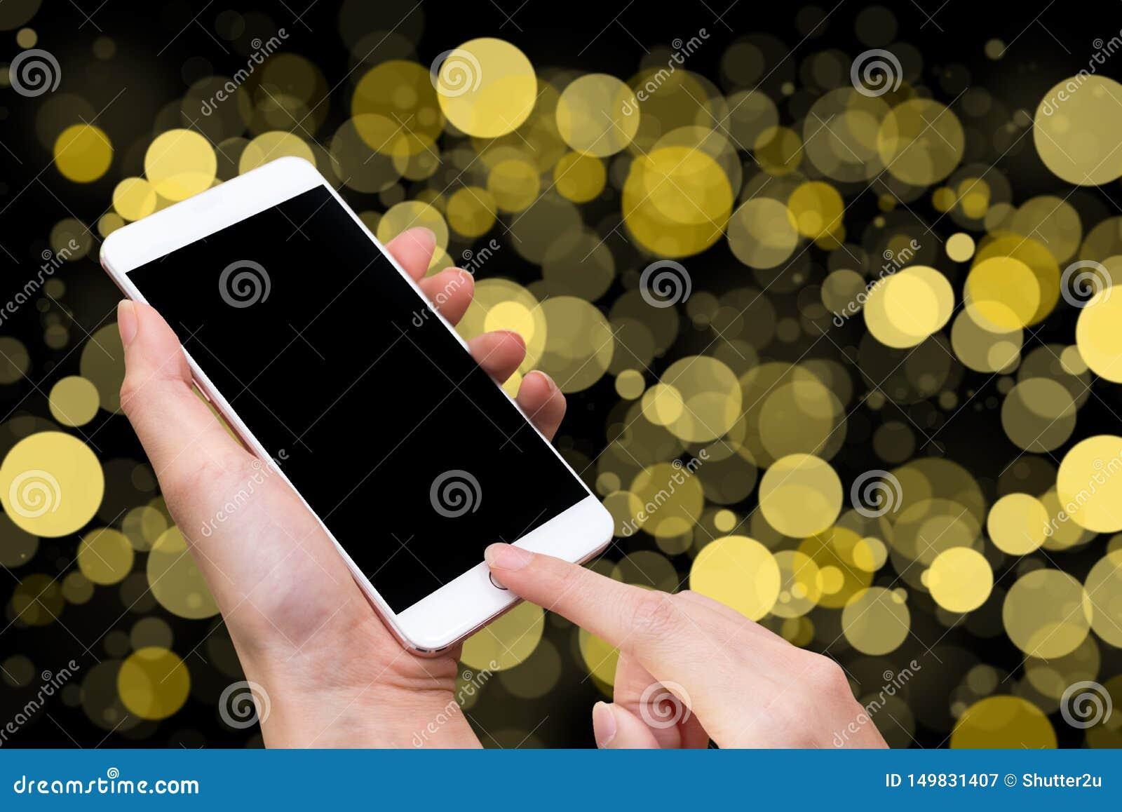 Smart telefon för kvinnahåll och handlagknapp vid handen med den tomma skärmen för annonsering, gul Bokeh suddighet och abstrakt