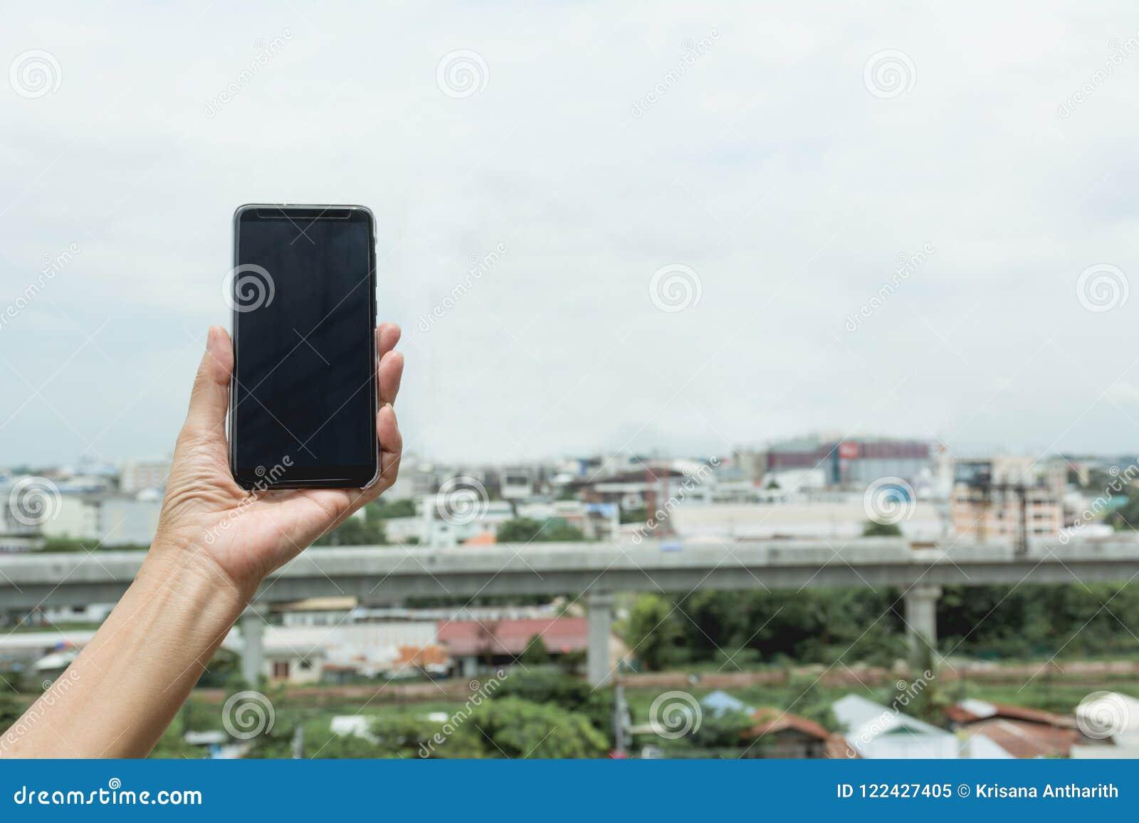 Smart telefon för kvinnahandinnehav med byggnadsbakgrund