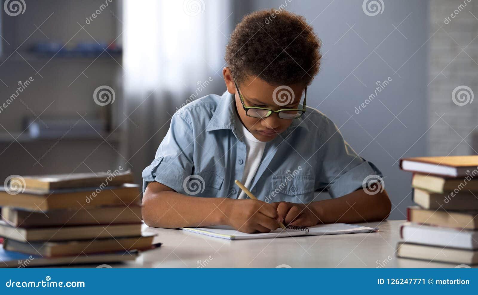 Smart weinig jongen die keurig thuiswerk in zijn notitieboekje schrijven, ijverige schooljongen