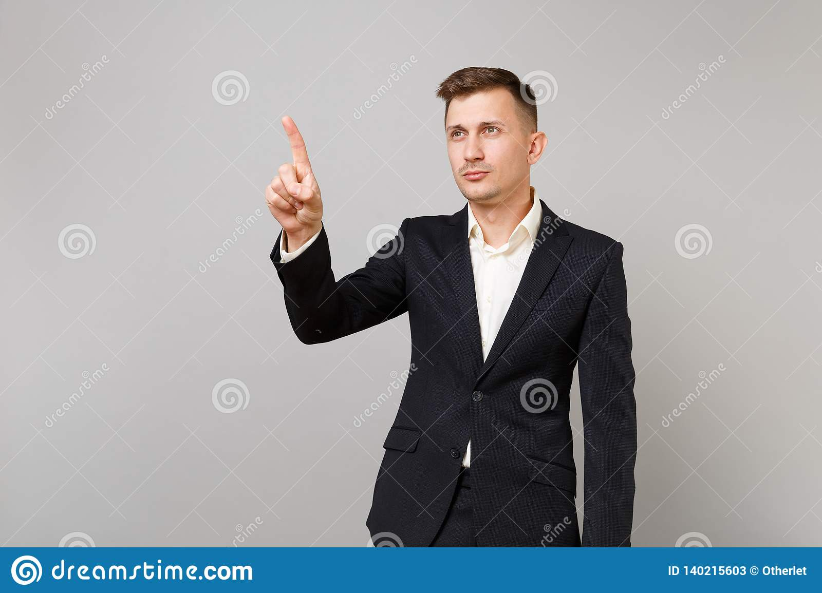 Smart young business man touch something like push click on button pointing at floating virtual screen isolated on grey