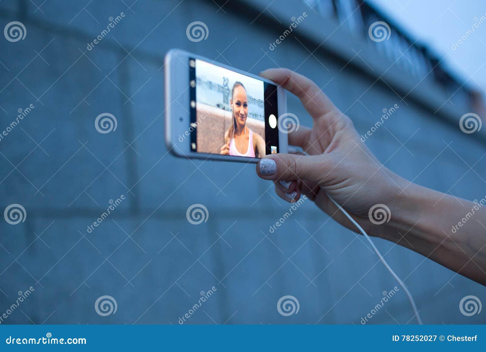 Smartphone κινηματογραφήσεων σε πρώτο πλάνο στο χέρι γυναικών που κάνει selfie