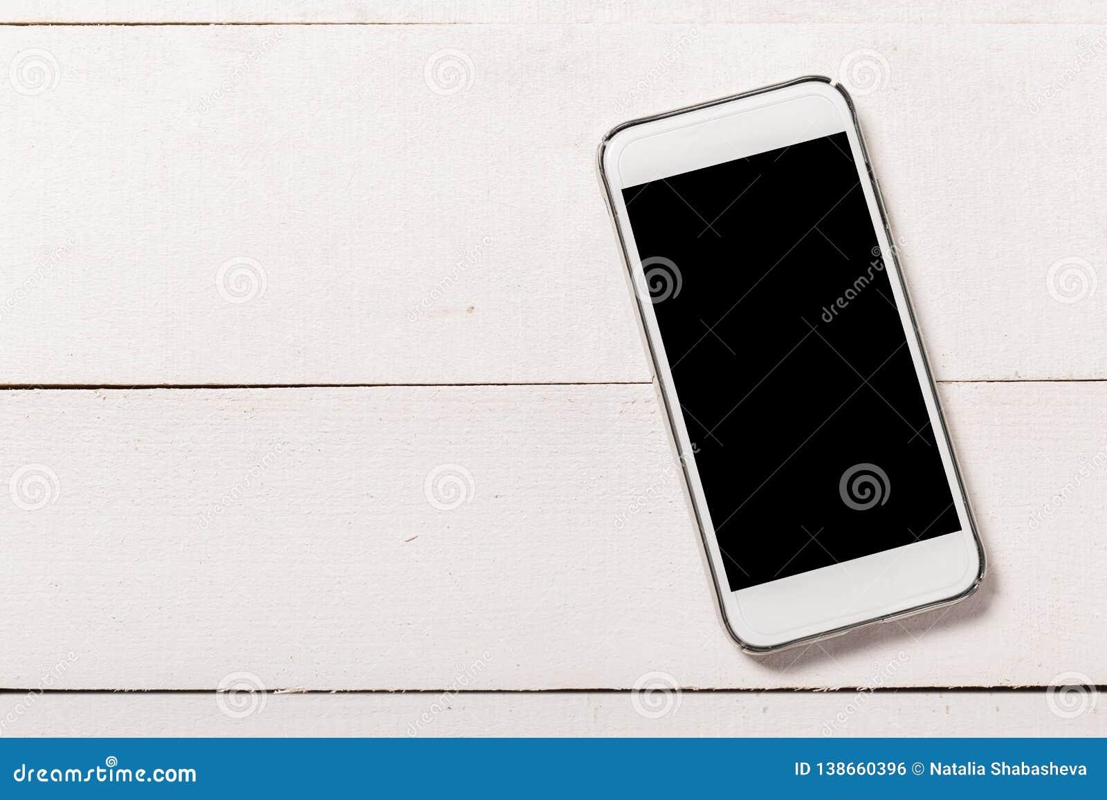 Smartphone στο ξύλινο υπόβαθρο σύστασης Τοπ όψη