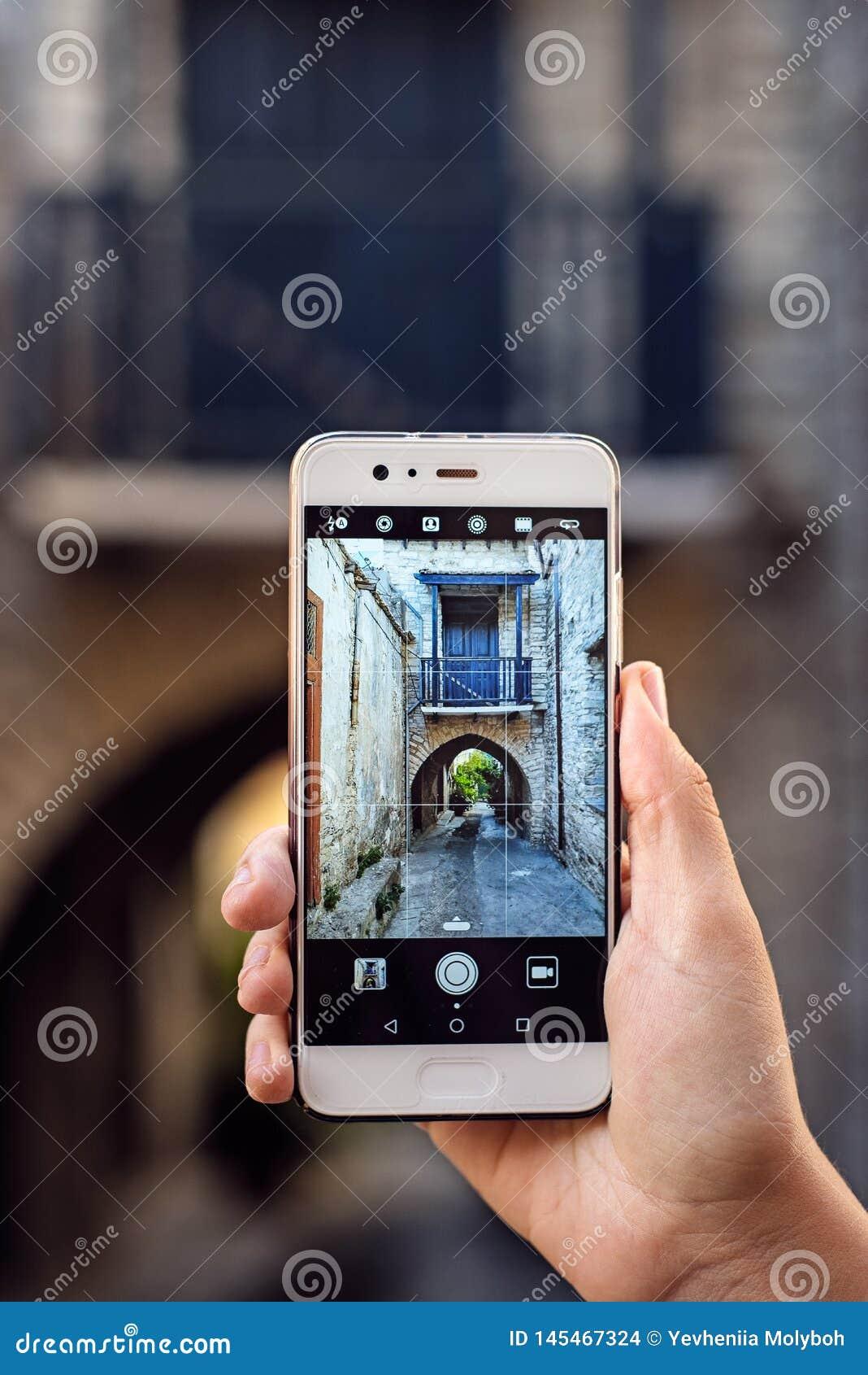 Туристская девушка принимая фото перемещения со смартфоном на летних отпусках Молодой привлекательный турист принимая фото selfie