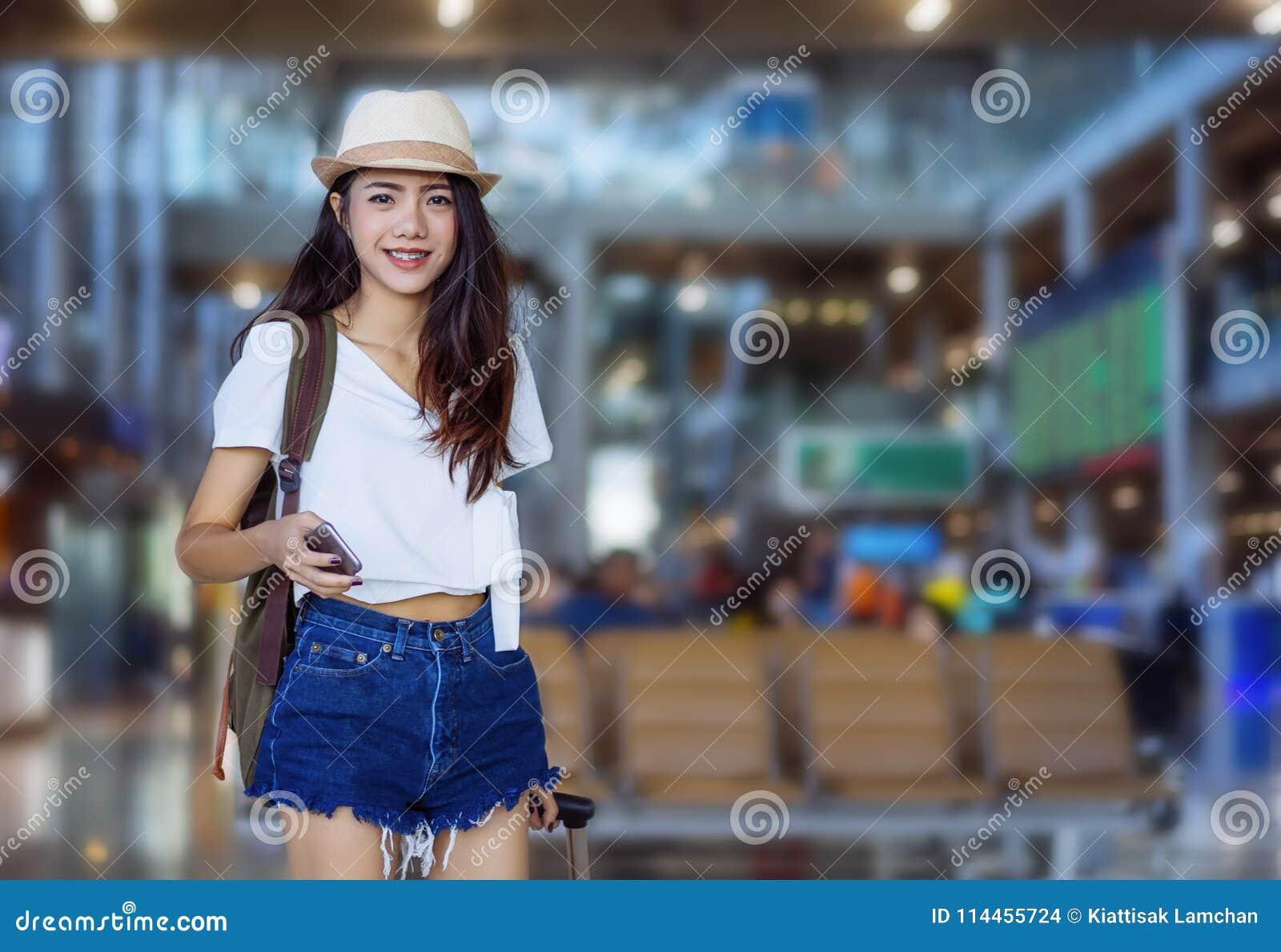 Smartphone asiático de la tenencia de la mujer en el aeropuerto