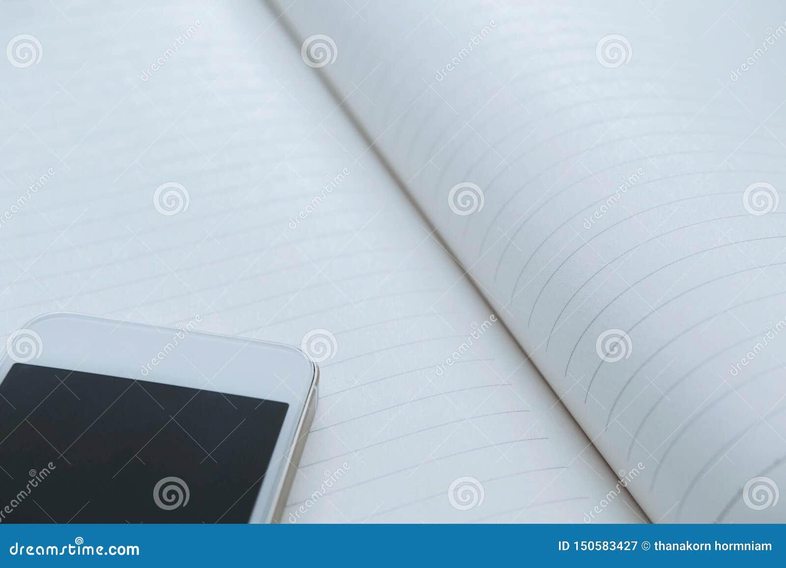 Smartphone bianco sul taccuino, spazio della copia