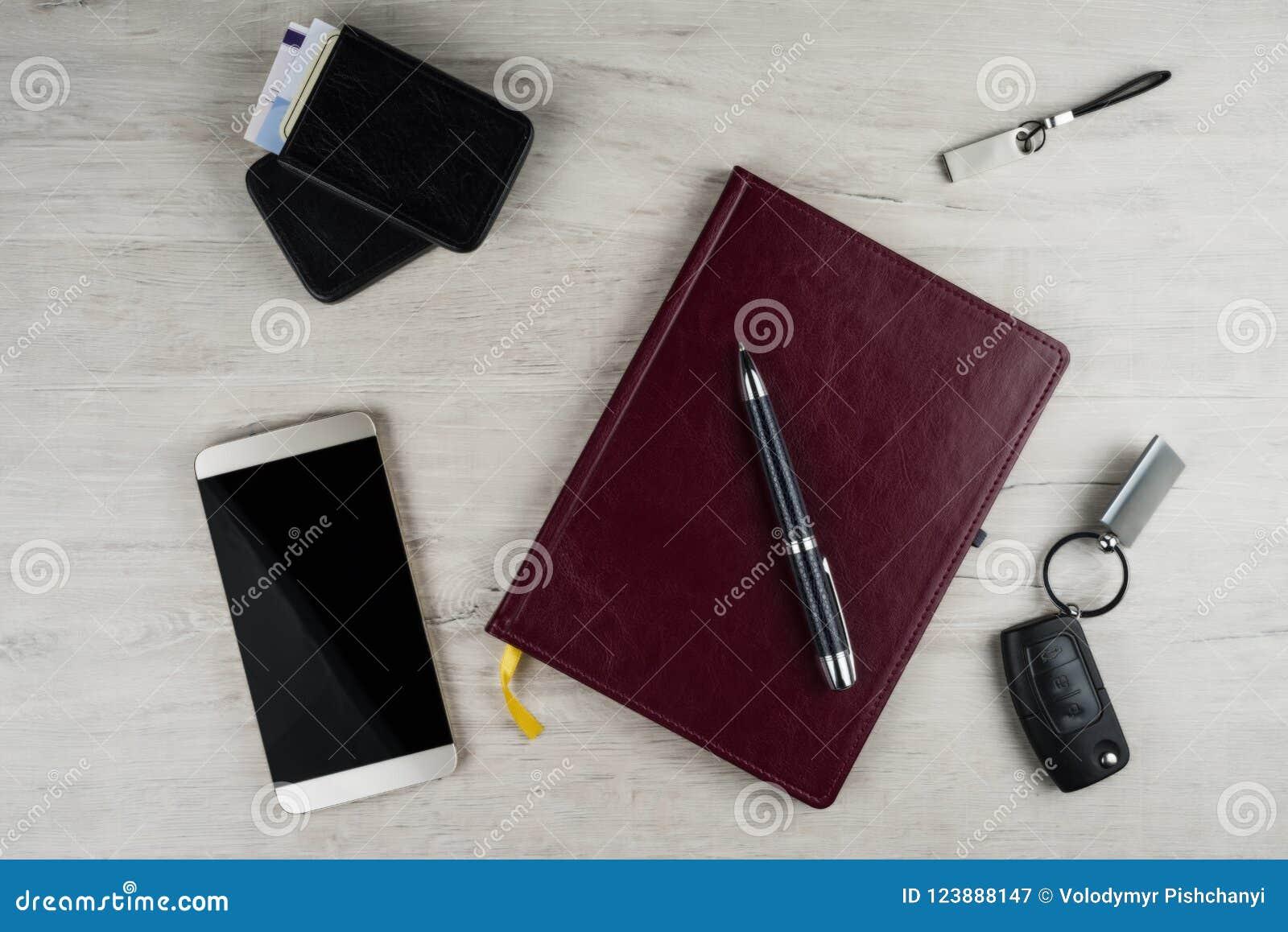 Smartphone, biurko ochraniacz, zapłonowy klucz, pióro i inni mężczyzna ` s akcesoria na powierzchni z teksturą bielący dąb,
