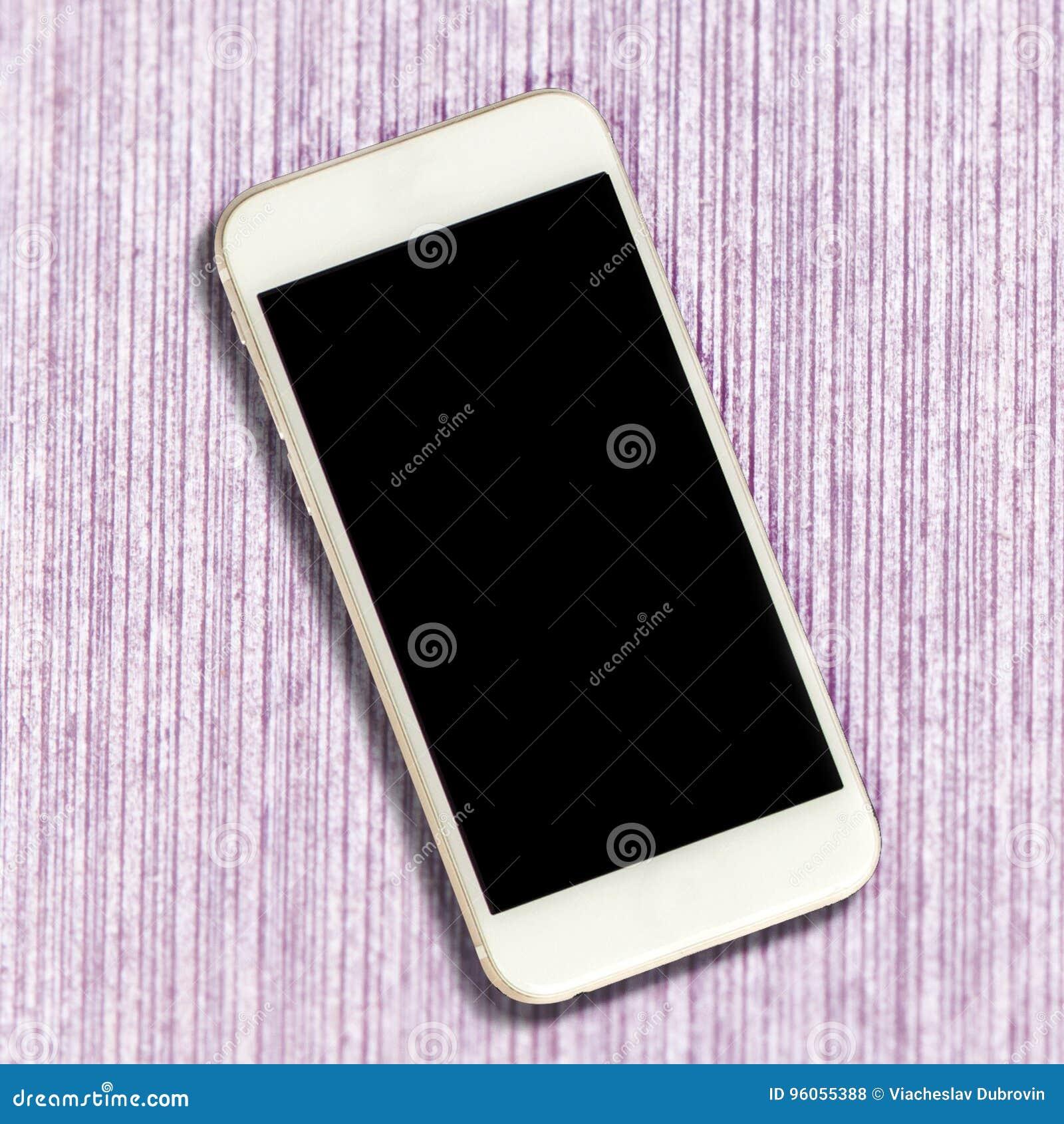Smartphone blanc avec l écran noir sur le fond rose de table