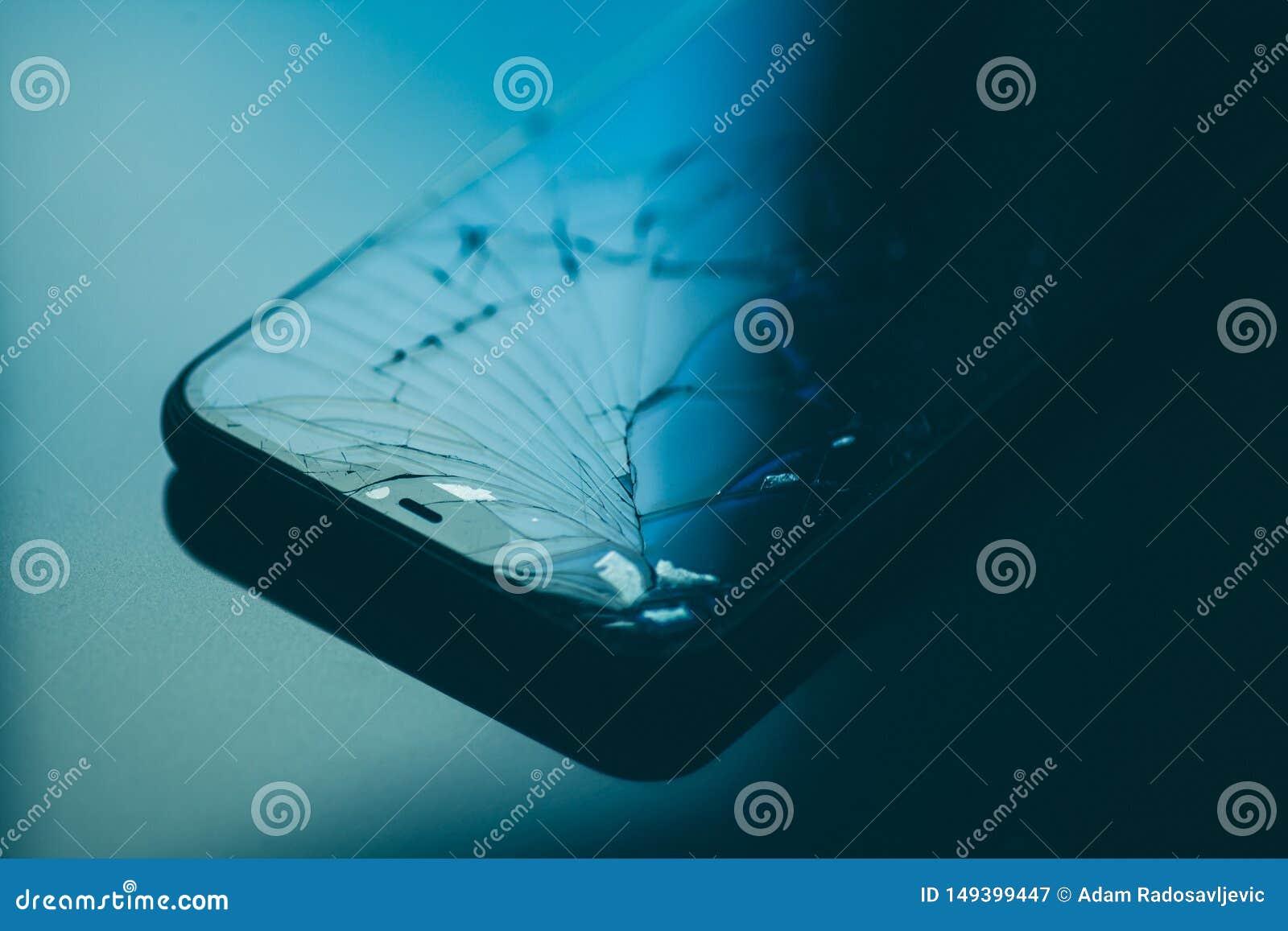 Smartphone with broken screen on black desktop