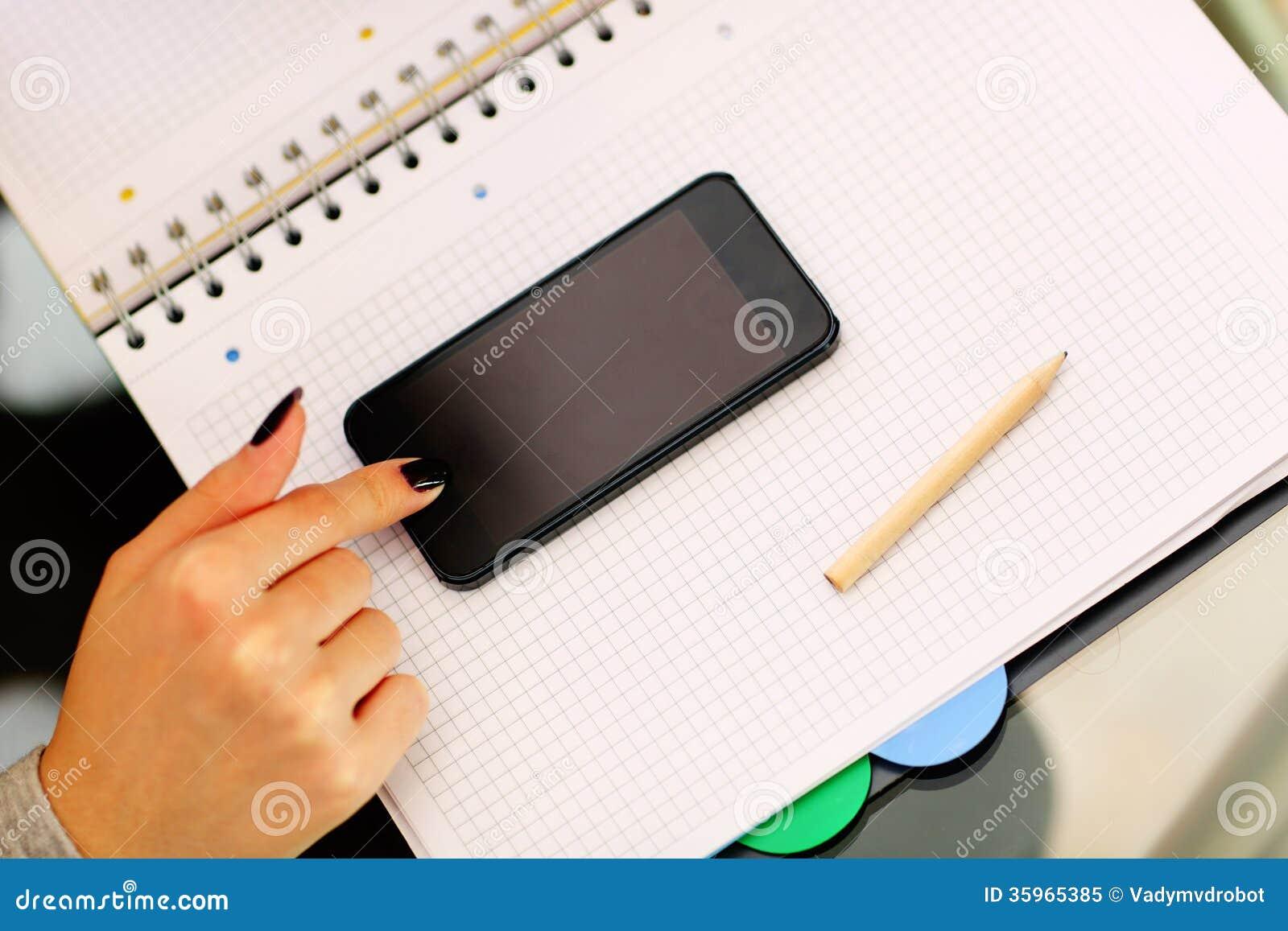 Smartphone conmovedor de la mano femenina