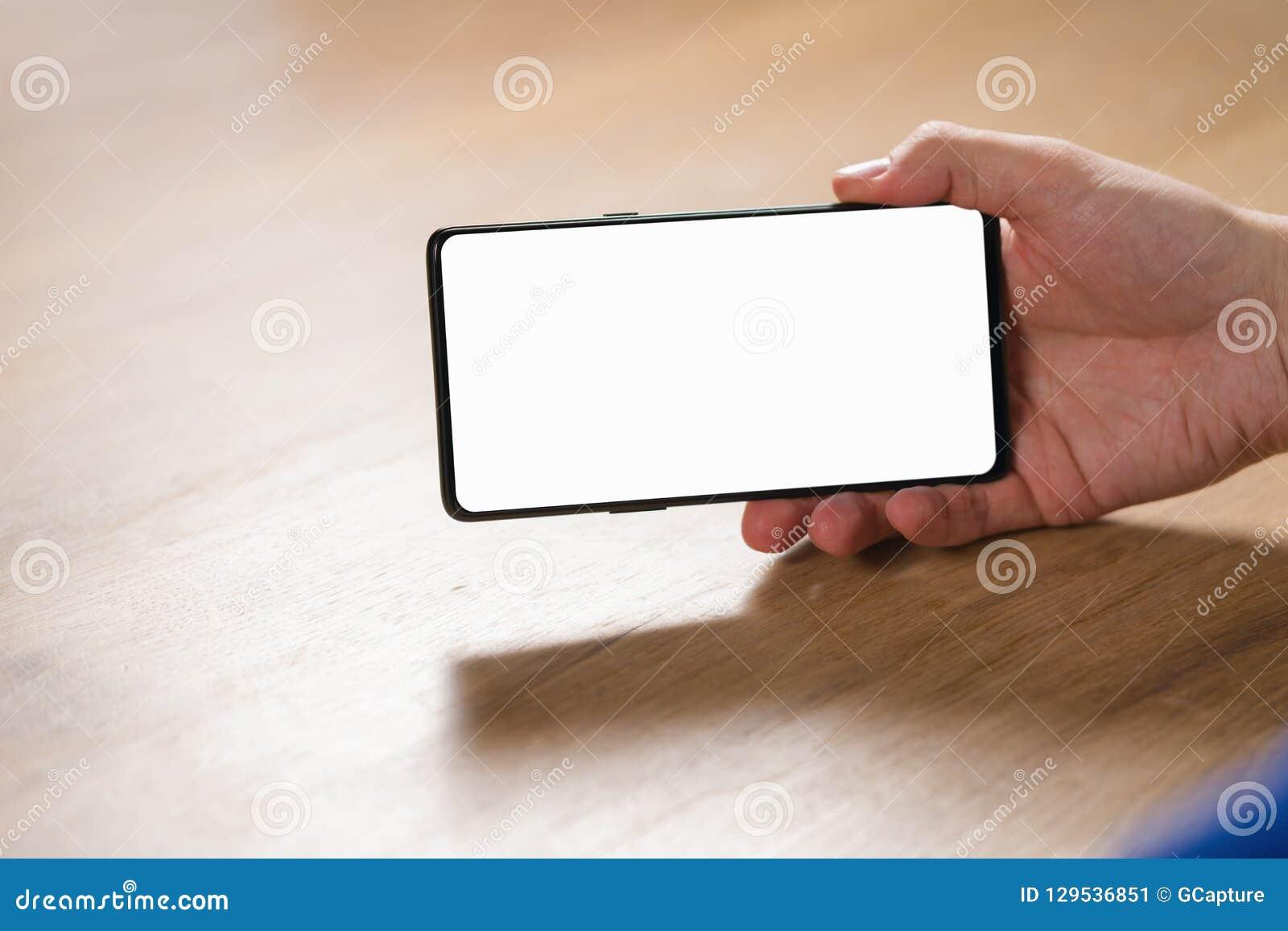 Smartphone da terra arrendada da mão do homem novo com a tela branca vazia no modo de paisagem