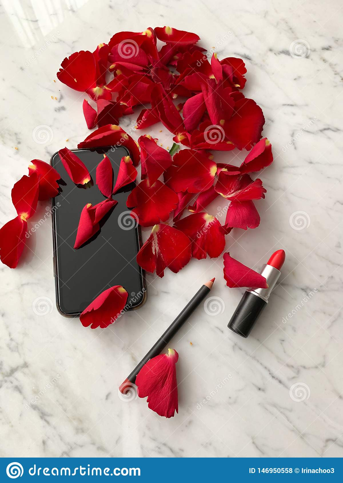 Smartphone dans la couleur noire de style d iphone avec les pétales de rose rouges et le rouge à lèvres rouge sur le fond de tabl