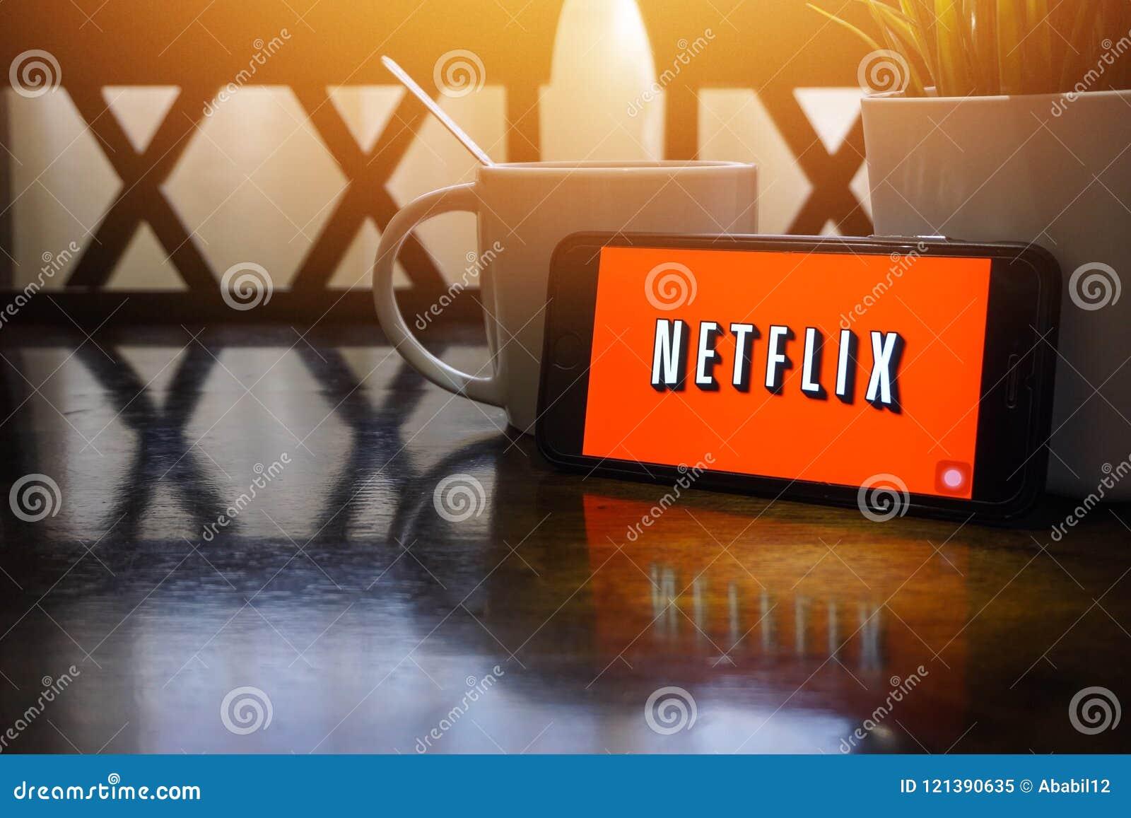 Smartphone, das Wort Netflix auf Holztisch mit Fragment des selektiven Fokus und der Ernte anzeigt