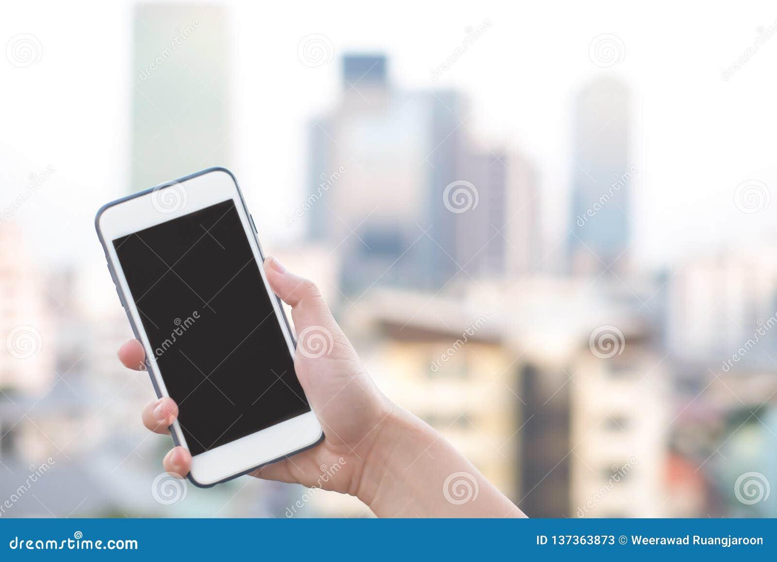 Smartphone de la tenencia de la mano o teléfono móvil con el fondo del edificio de la ciudad y el espacio de la copia