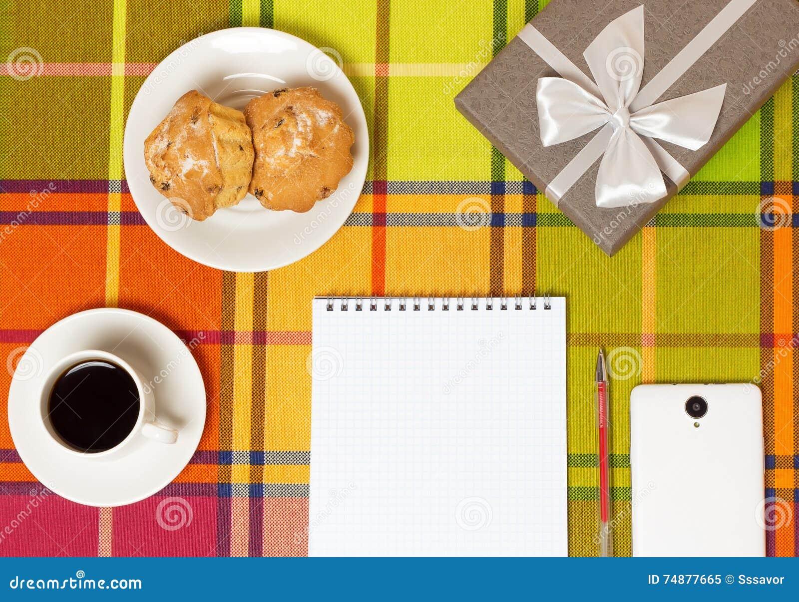 Smartphone dei muffin del caffè sulla tavola