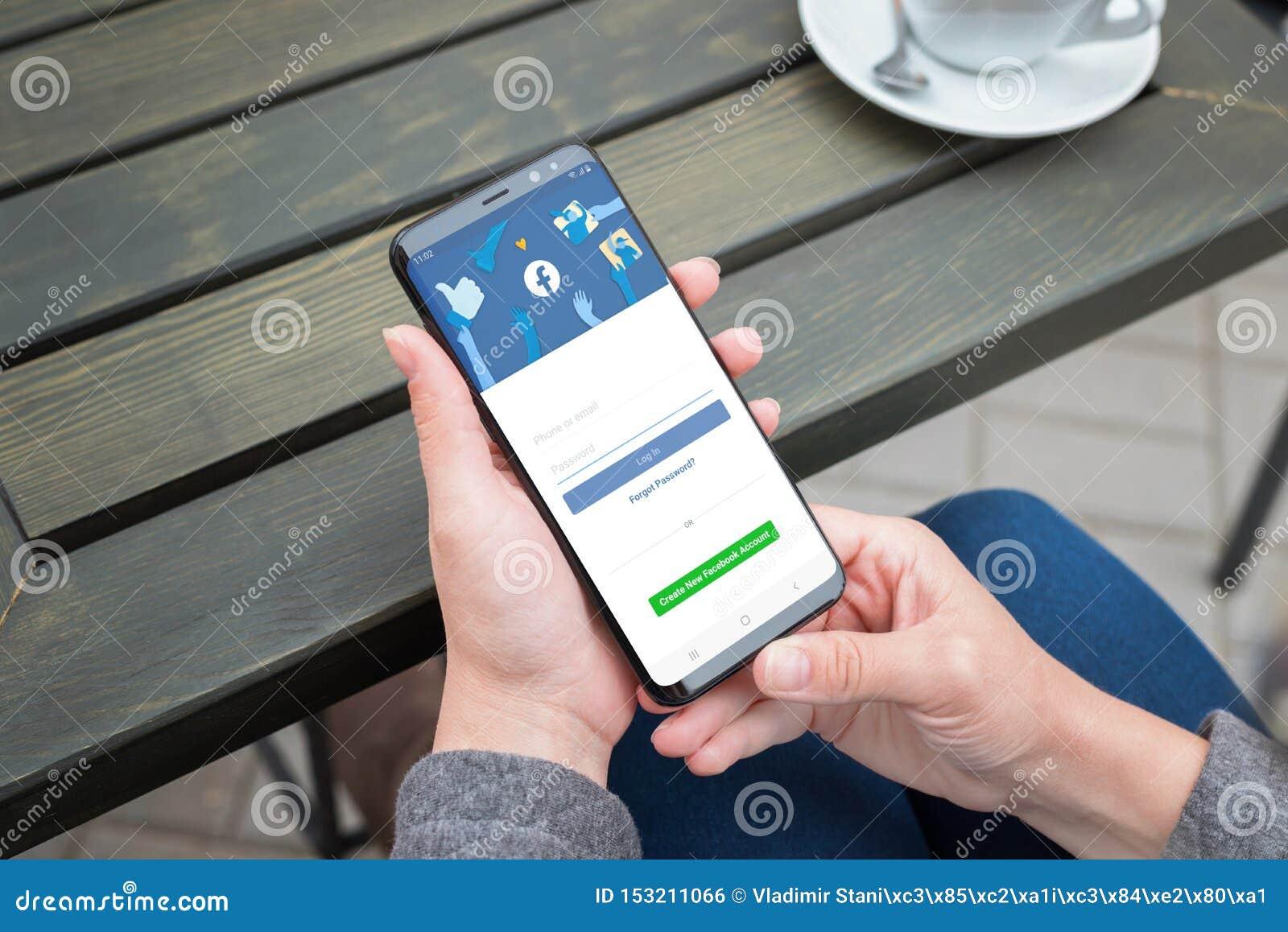 Smartphone del Samsung Galaxy del uso de la mujer a abrirse una sesión en la cuenta social de la red de Facebook