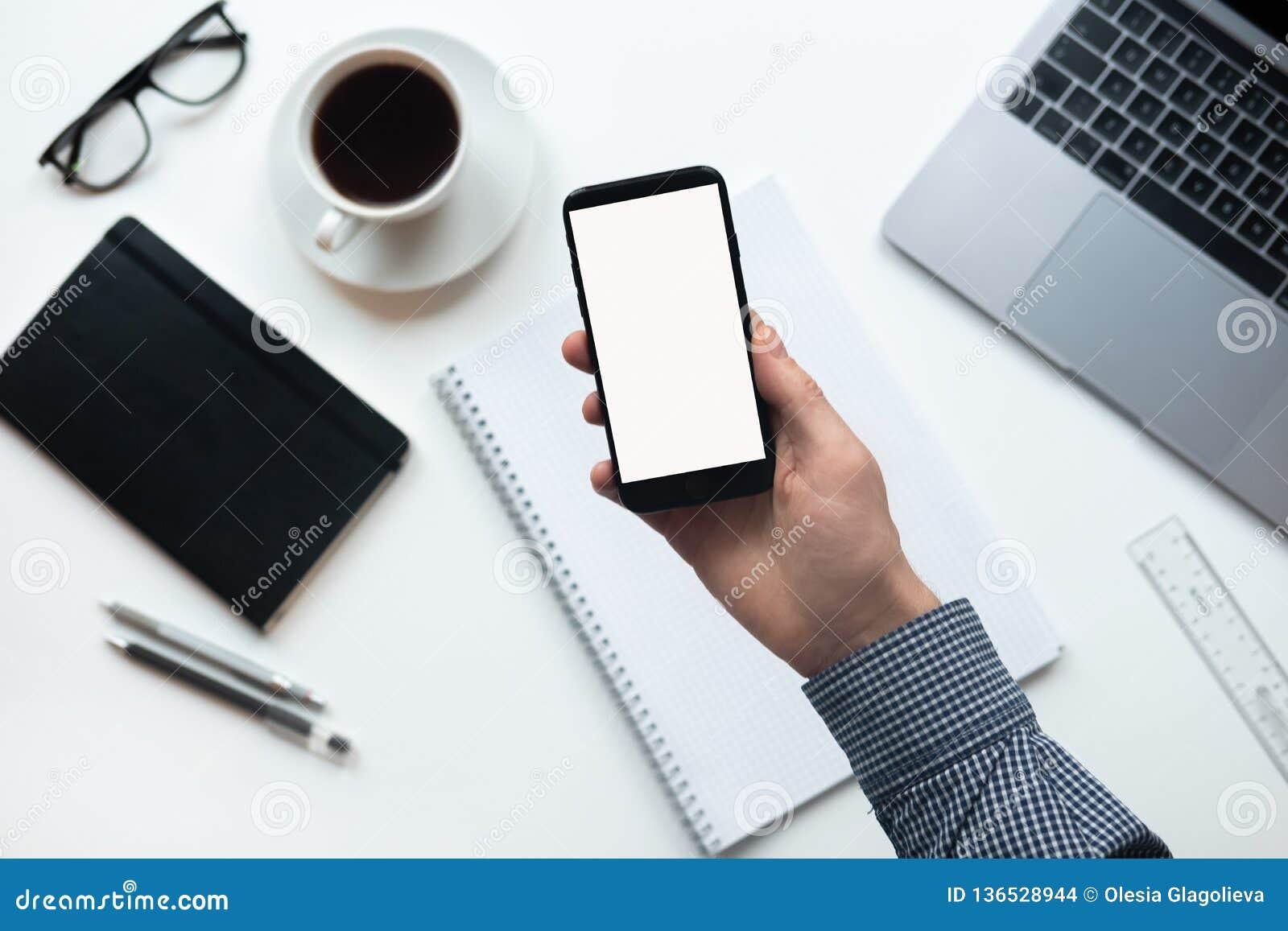 Smartphone di uso della mano sulla tavola dell ufficio Smartphone del cellulare della tenuta dell uomo