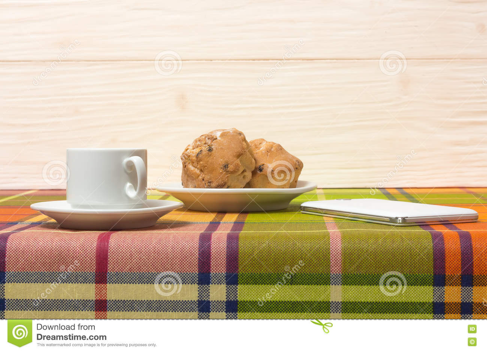 Smartphone dos queques do café na tabela