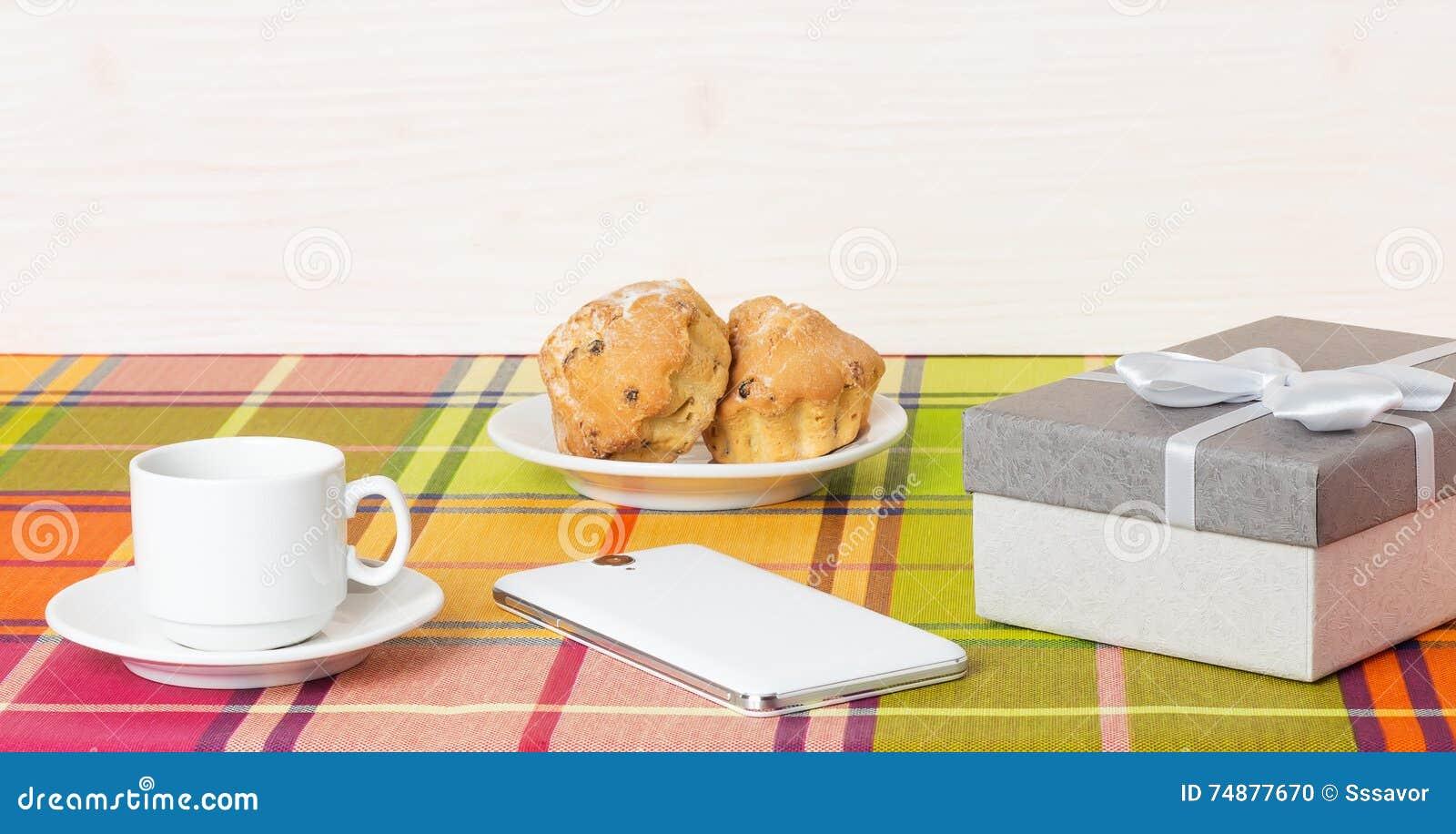 Smartphone dos queques do copo de café na tabela