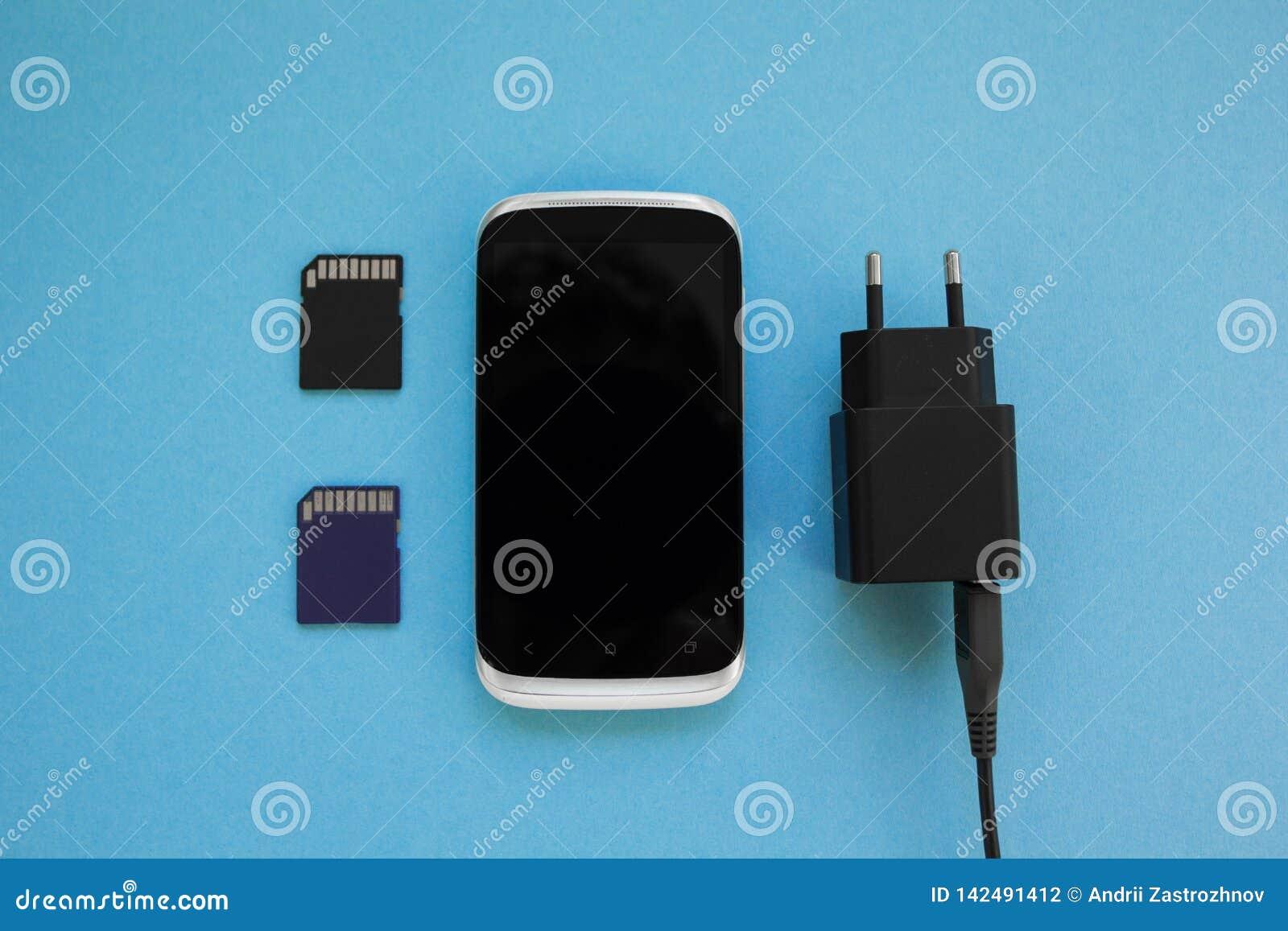 Smartphone, een twee geheugenkaart en een lader op een blauwe achtergrond