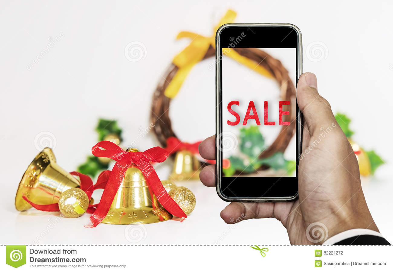 Smartphone on hand with `SALE` on screen, with Christmas decorations ornament, Holiday Christmas Sale