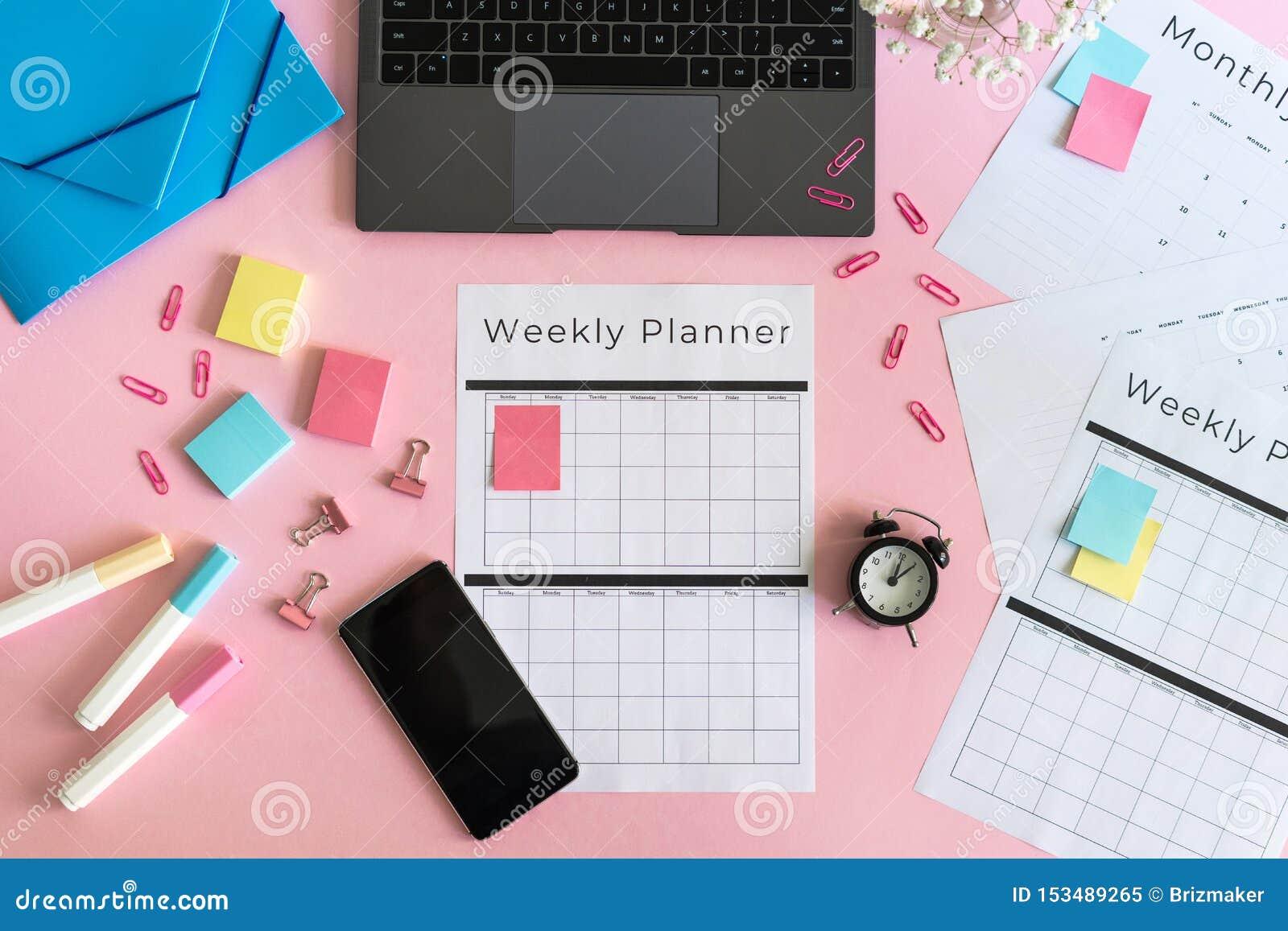 Smartphone, laptop, kantoorbehoeften en ontwerper op roze pastelkleurachtergrond