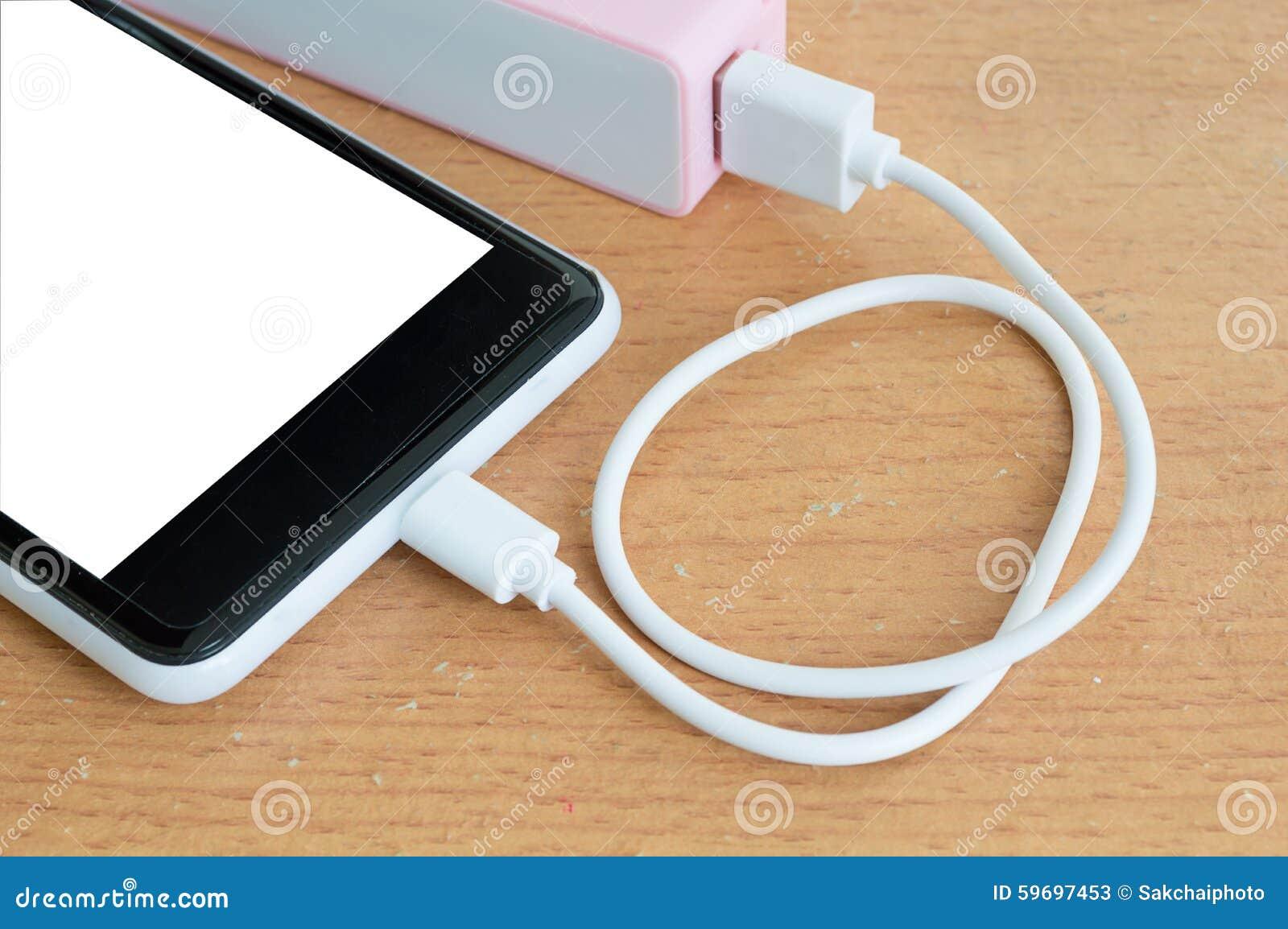 Smartphone med rosa powerbank på det wood skrivbordet