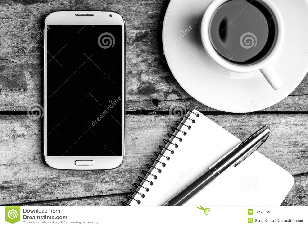 Smartphone with notebook, fountain pen and cup of coffee.