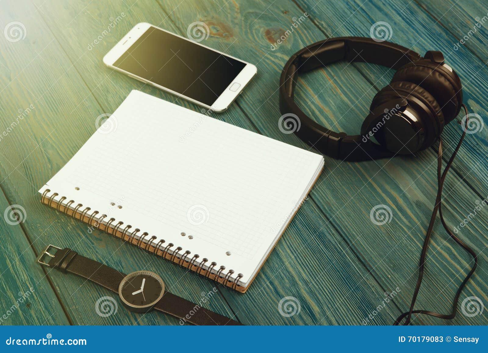 Smartphone, notepad, hörlurar och klocka