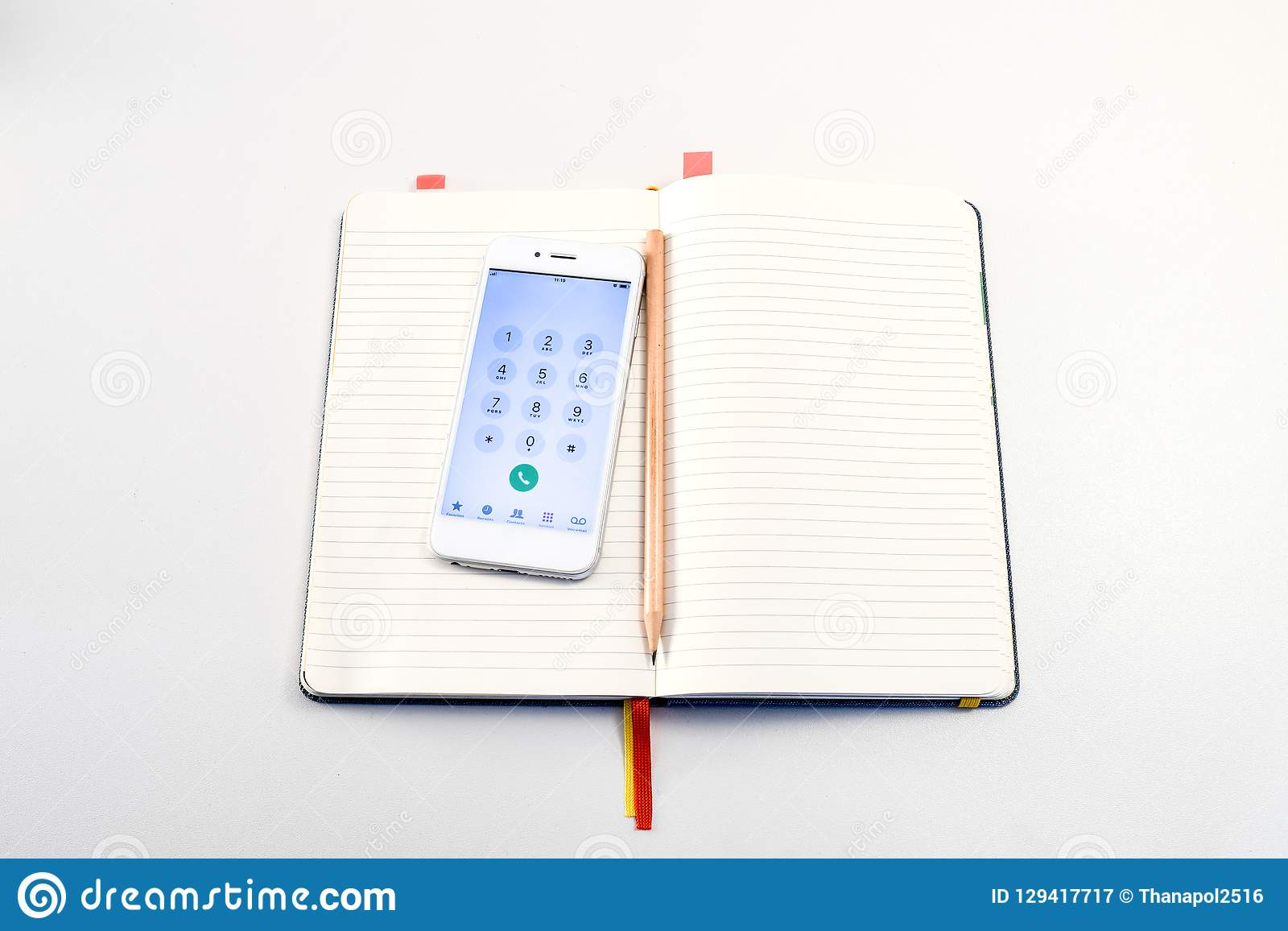 Smartphone and pencil in the book on the white table