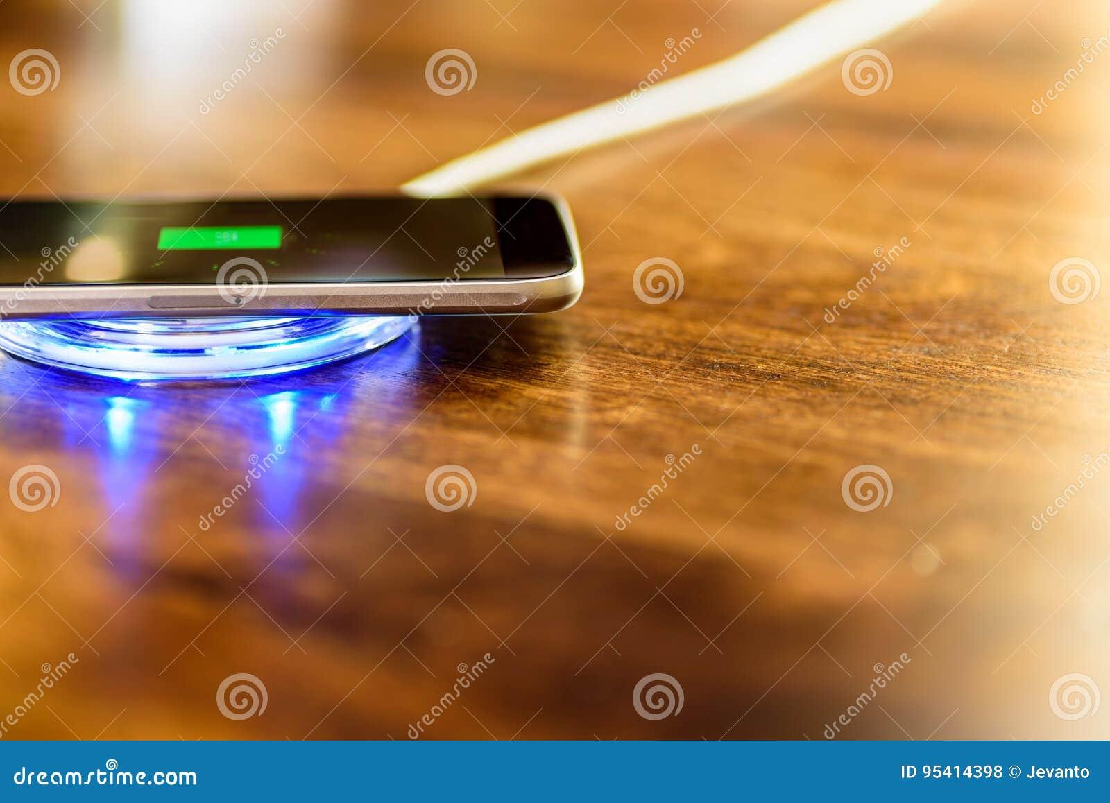 Smartphone que carrega em uma almofada de carregamento Cobrar sem fio