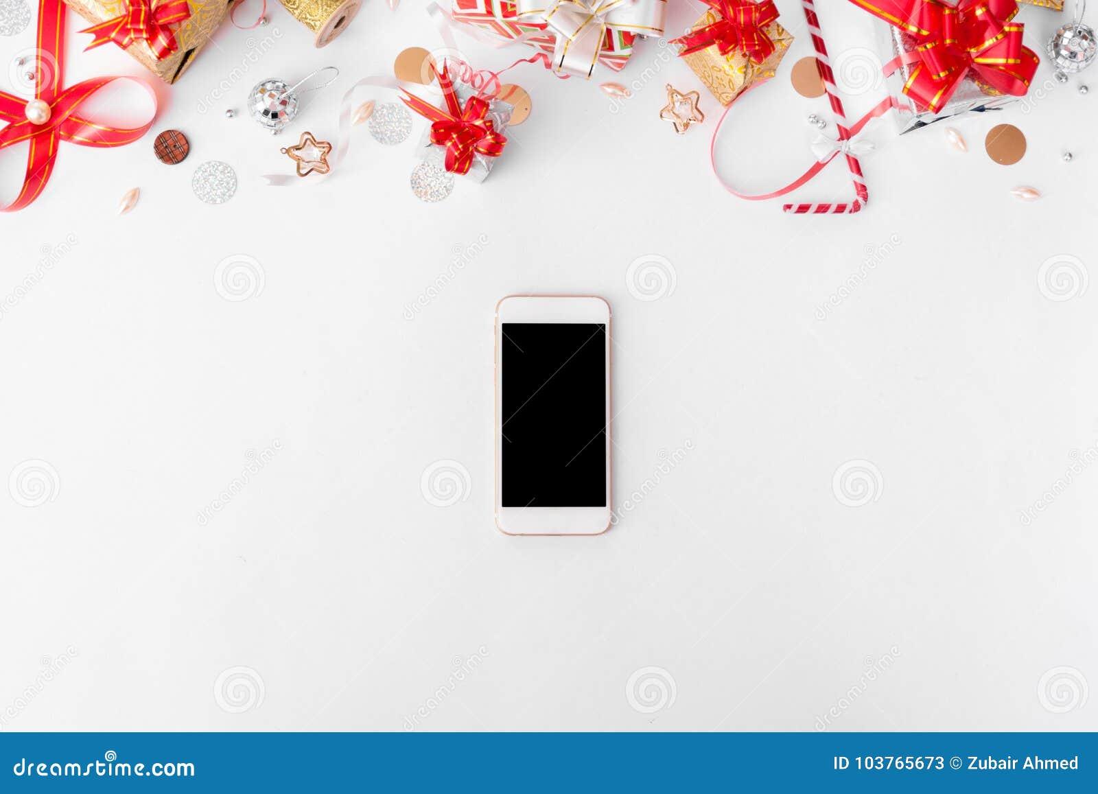 Smartphone-samenstelling voor Kerstmistijd Kerstmisgiften en decoratie op witte achtergrond