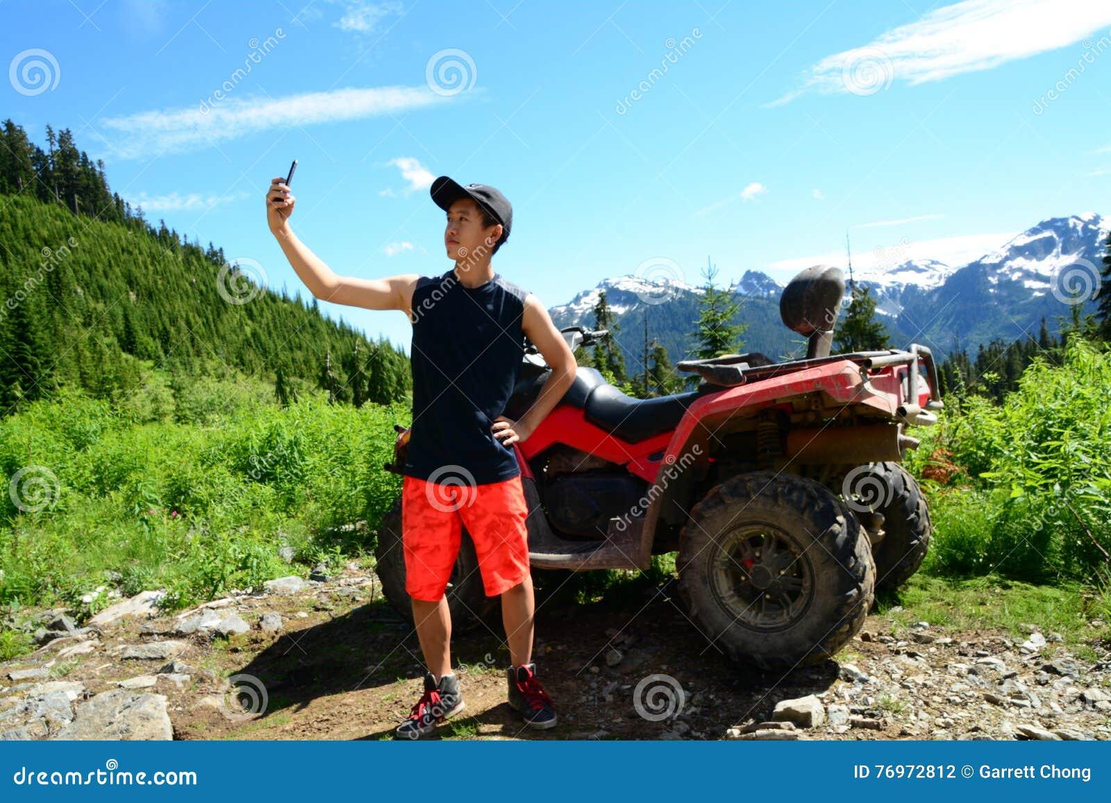 Smartphone Selfie door Generatiey Tiener met ATV & x28; Vehicle& geschikt voor elk terrein x29; Geparkeerd in Bergachtig Forest N