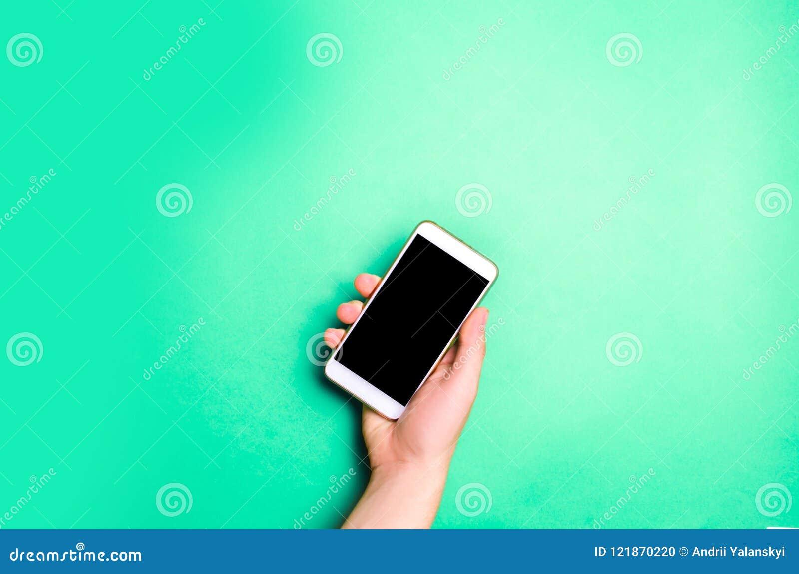 Smartphone, telefono in mani maschii su un fondo verde Il concetto della comunicazione uso degli aggeggi, tecnologie moderne Soci