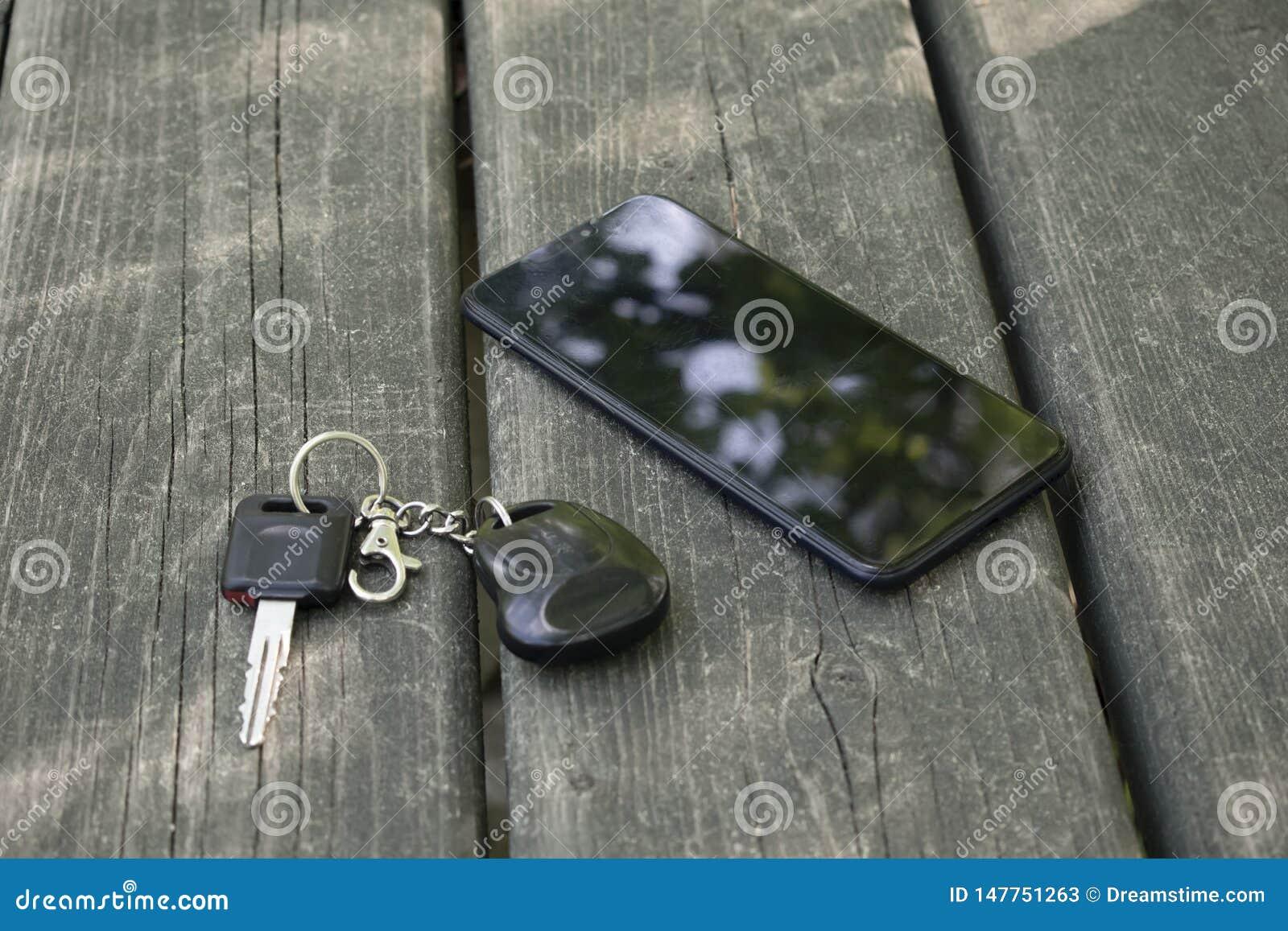 Smartphone und Autoschlüssel liegen auf einem Holztisch