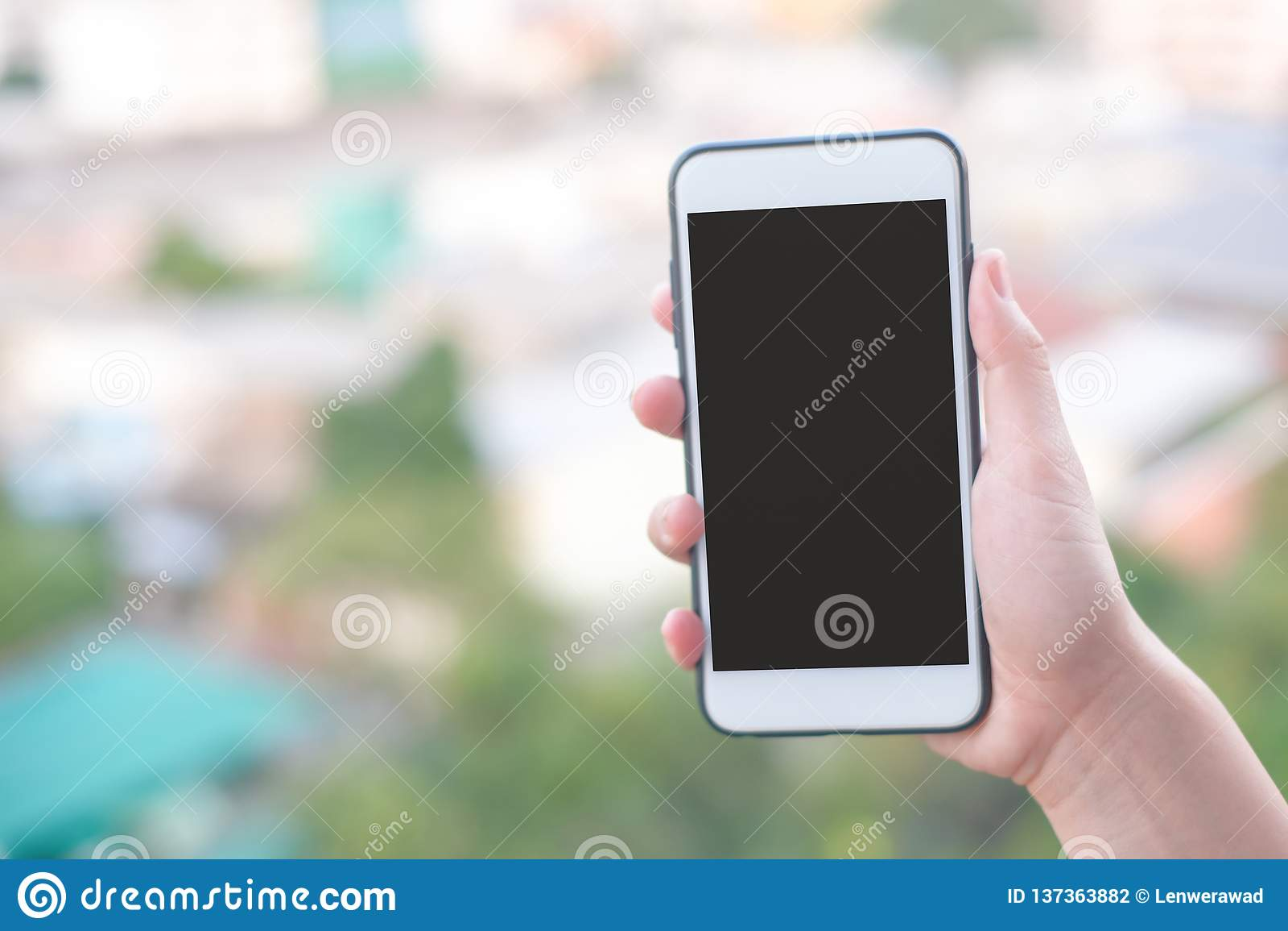 Smartphone van de handholding of mobiele telefoon met stad de bouwachtergrond en exemplaarruimte